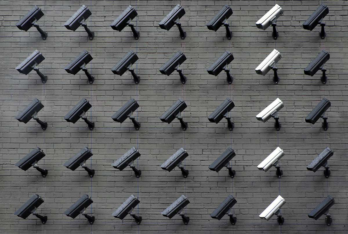 Photo showing a grid of security cameras mounted to a wall