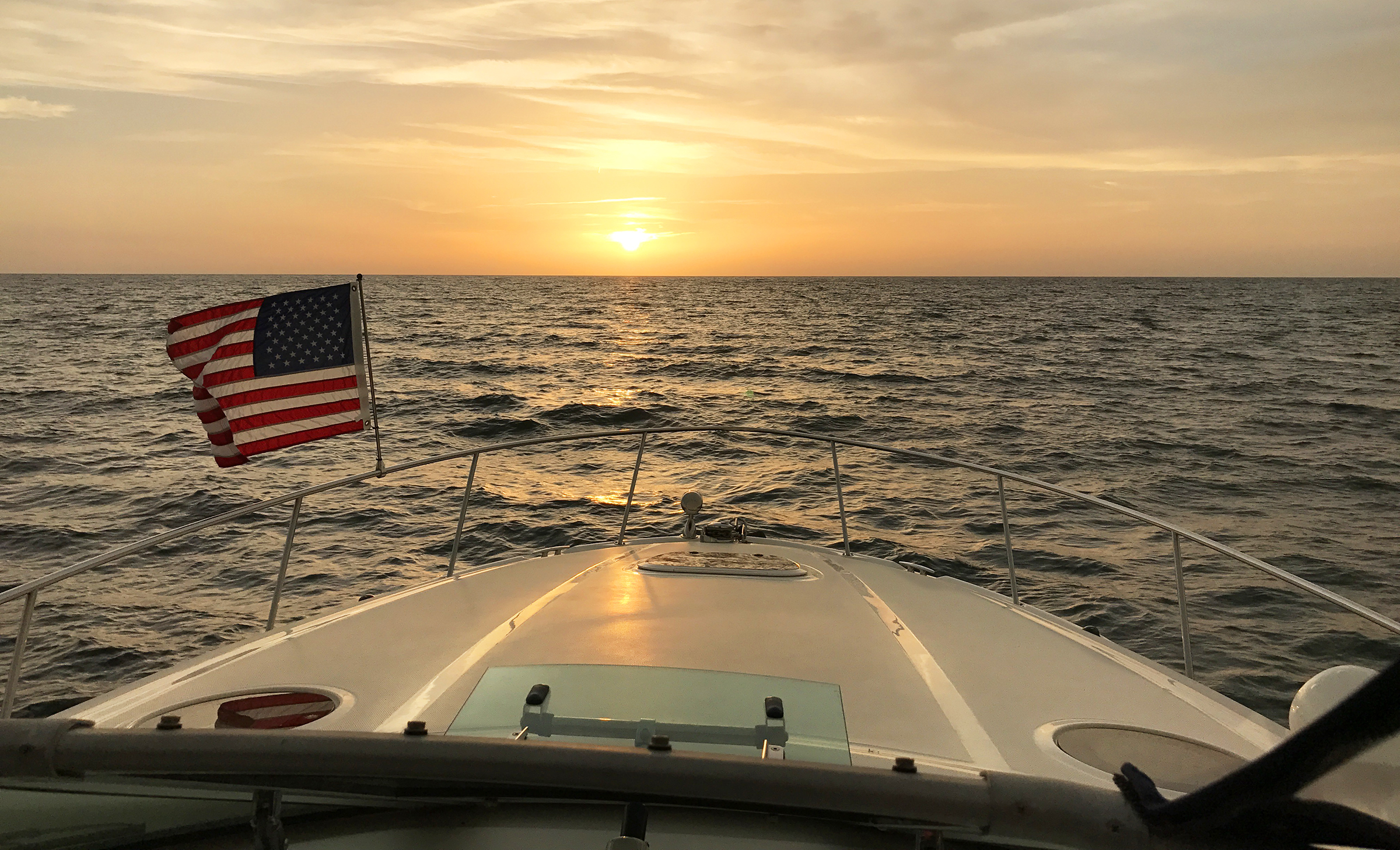 Front of boat with American flag cruising off gulf coast of Florida