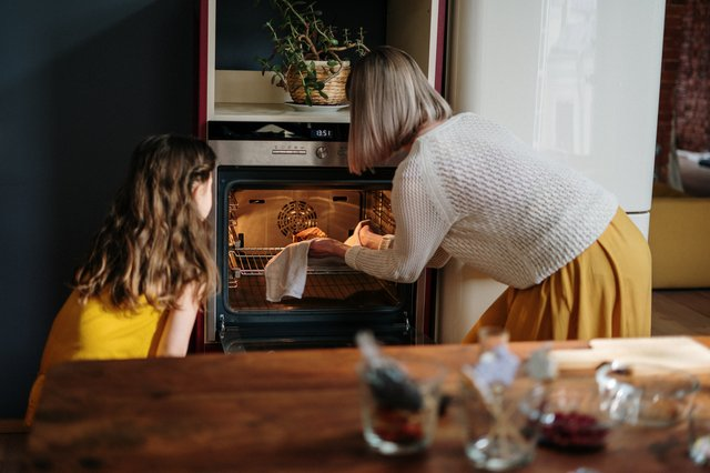 mom and daughter using oven