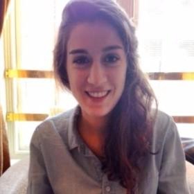 photographie d'une jeune femme souriant aux cheveux longs et bruns