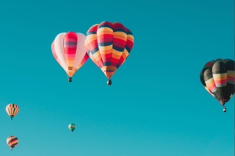 photographie de plusieurs montgolfières colorées dans un ciel bleu et ensoleillé
