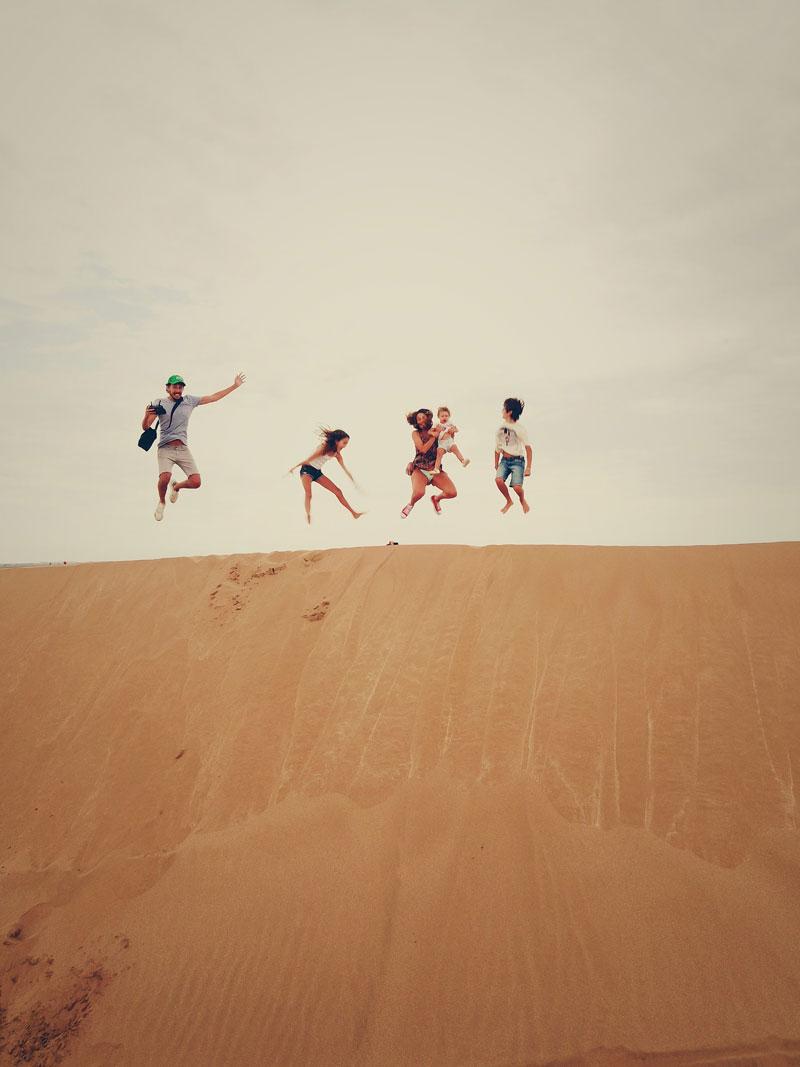 photographie couleur d'une famille dans un désert en train de sauter
