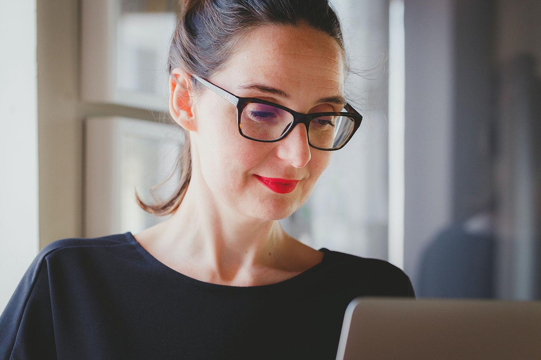photographie d'une femme portant des lunettes regardant son ordinateur