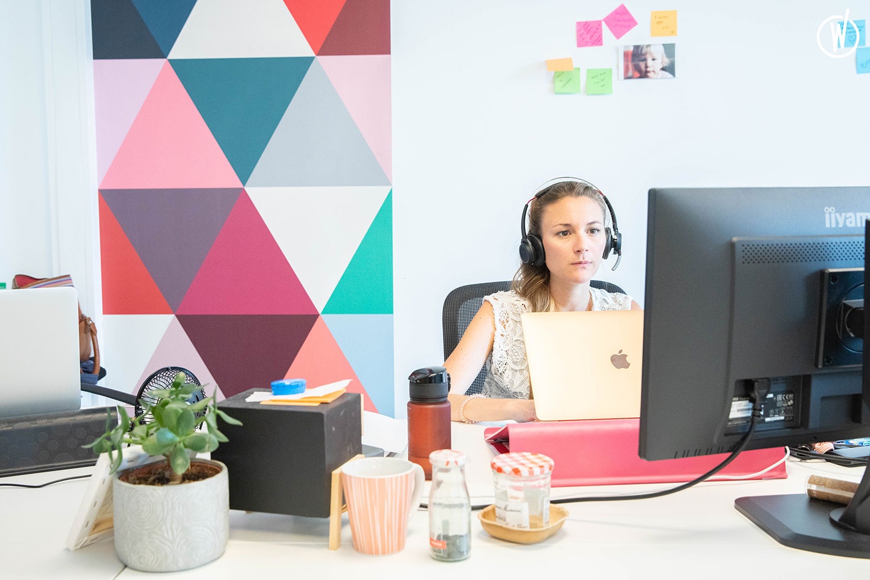 photographie d'une jeune femme à son bureau prenant des appels téléphoniques