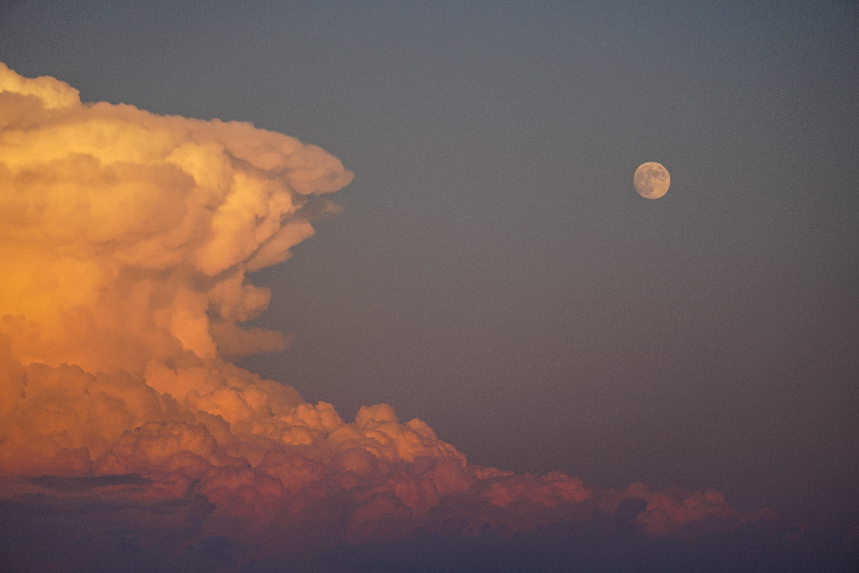 photographie d'un ciel avec des nuages roses et de la lune