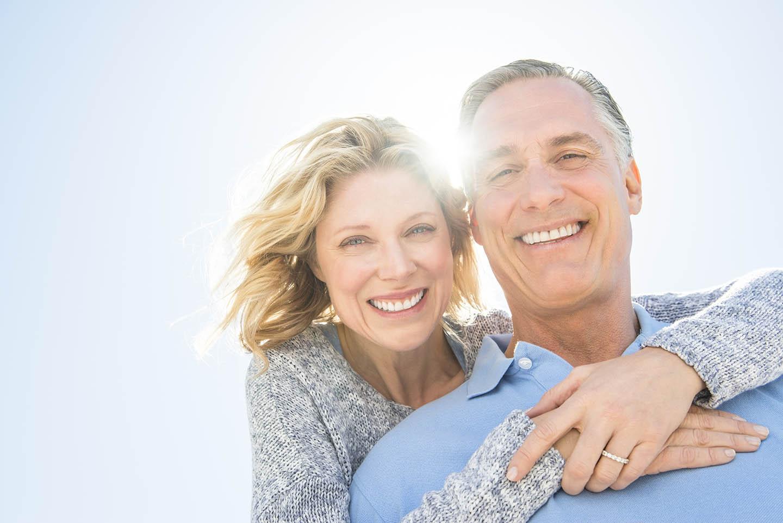 couple smiling outside hugging