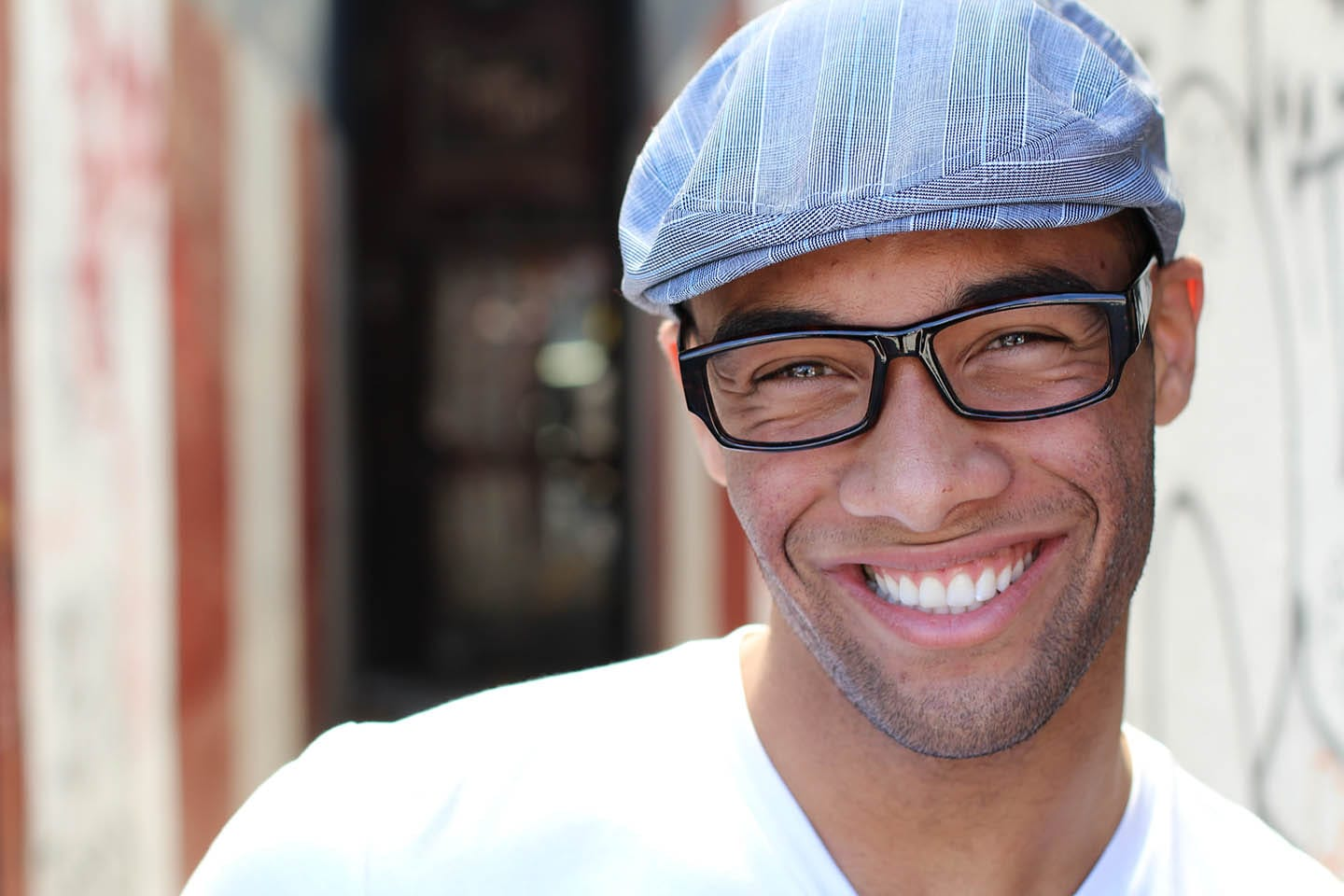 man wearing hat and glasses smiling