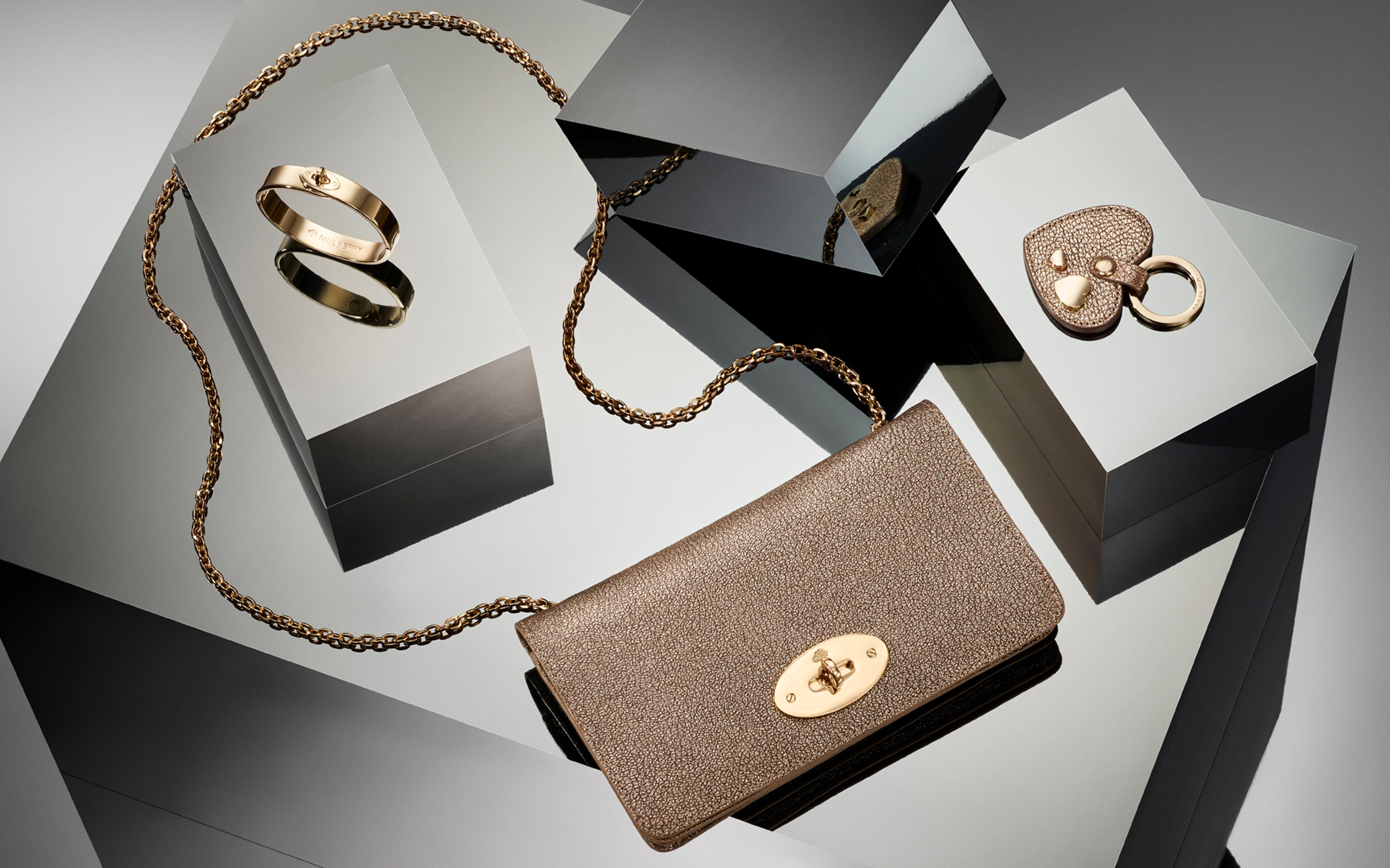 creative commercial shot of handbags and accessories in a light grey reflecting scene