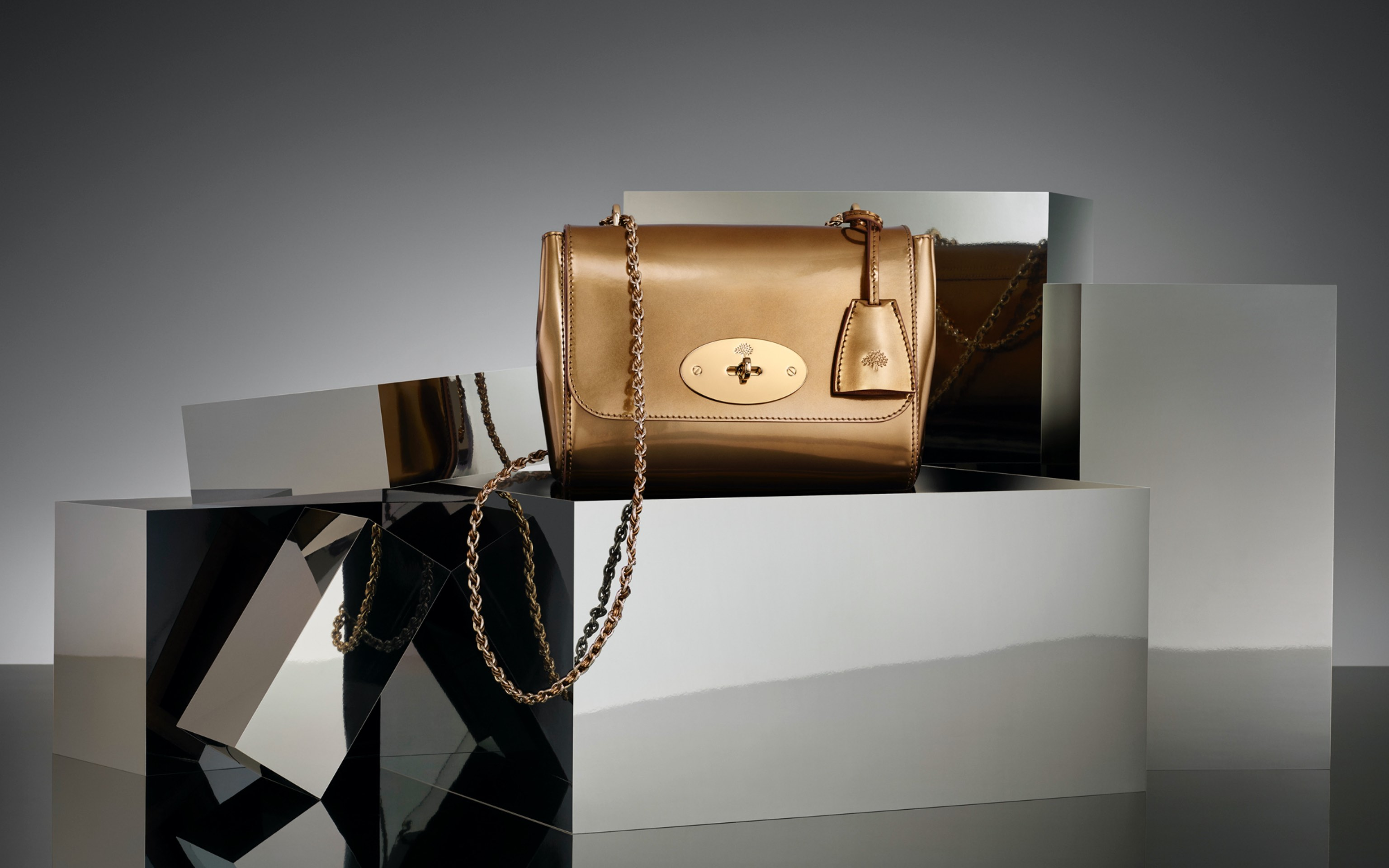 creative commercial shot of gold colour bag in grey reflecting scene