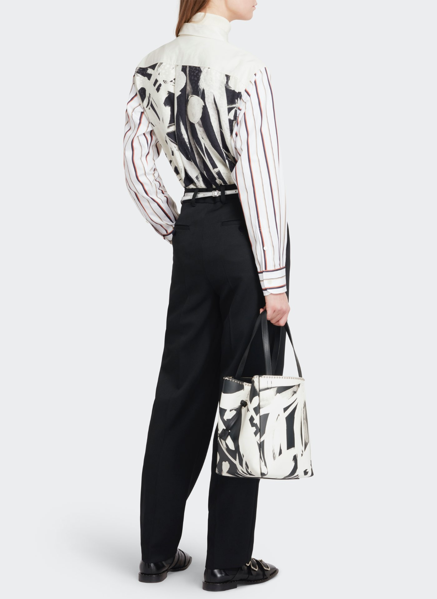 Womenswear model wearing black trousers and white and black pattern shirt with a black and white pattern leather bag