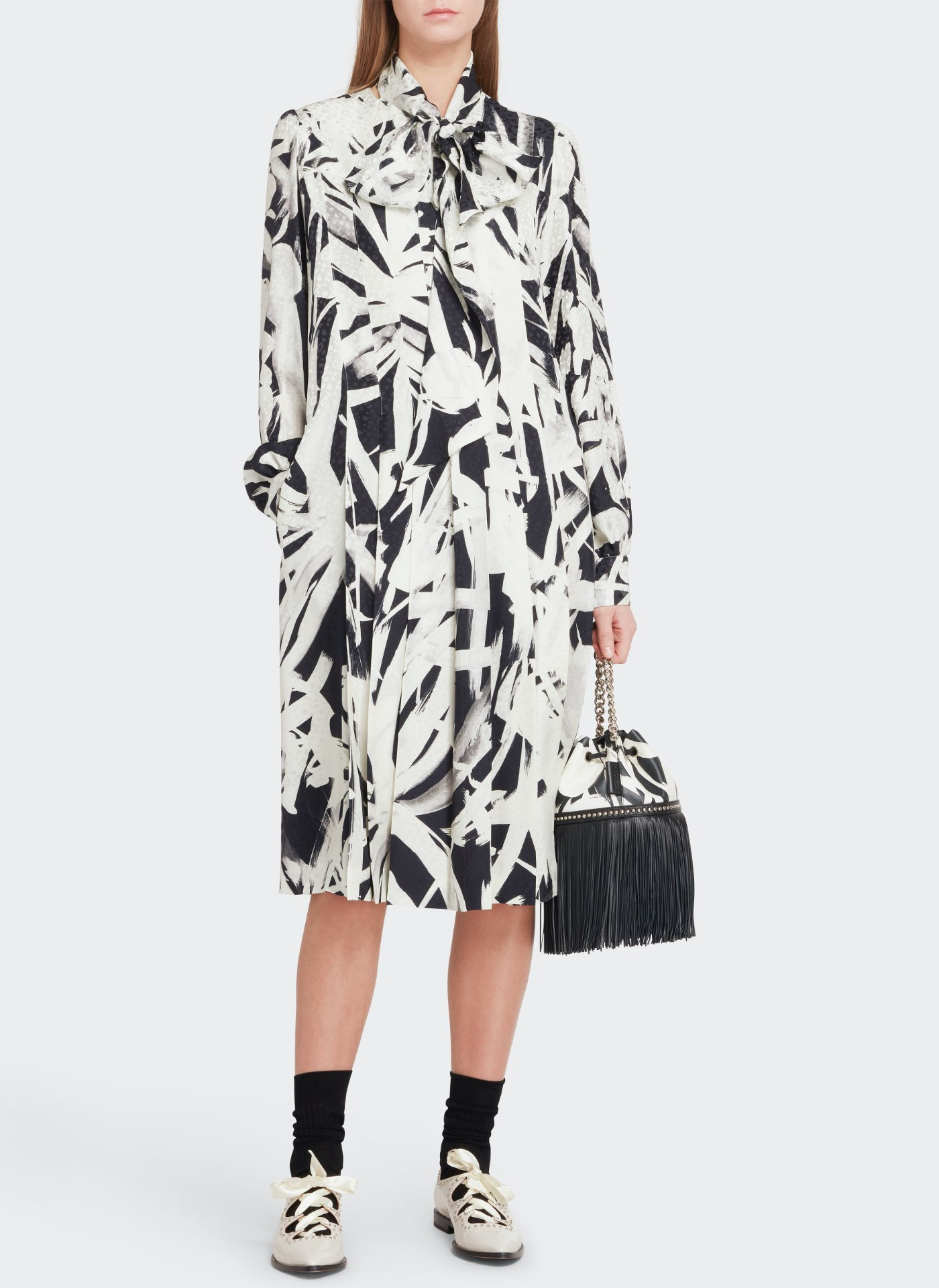 Womenswear model wearing a white and black pattern J&M dress with a black leather bag