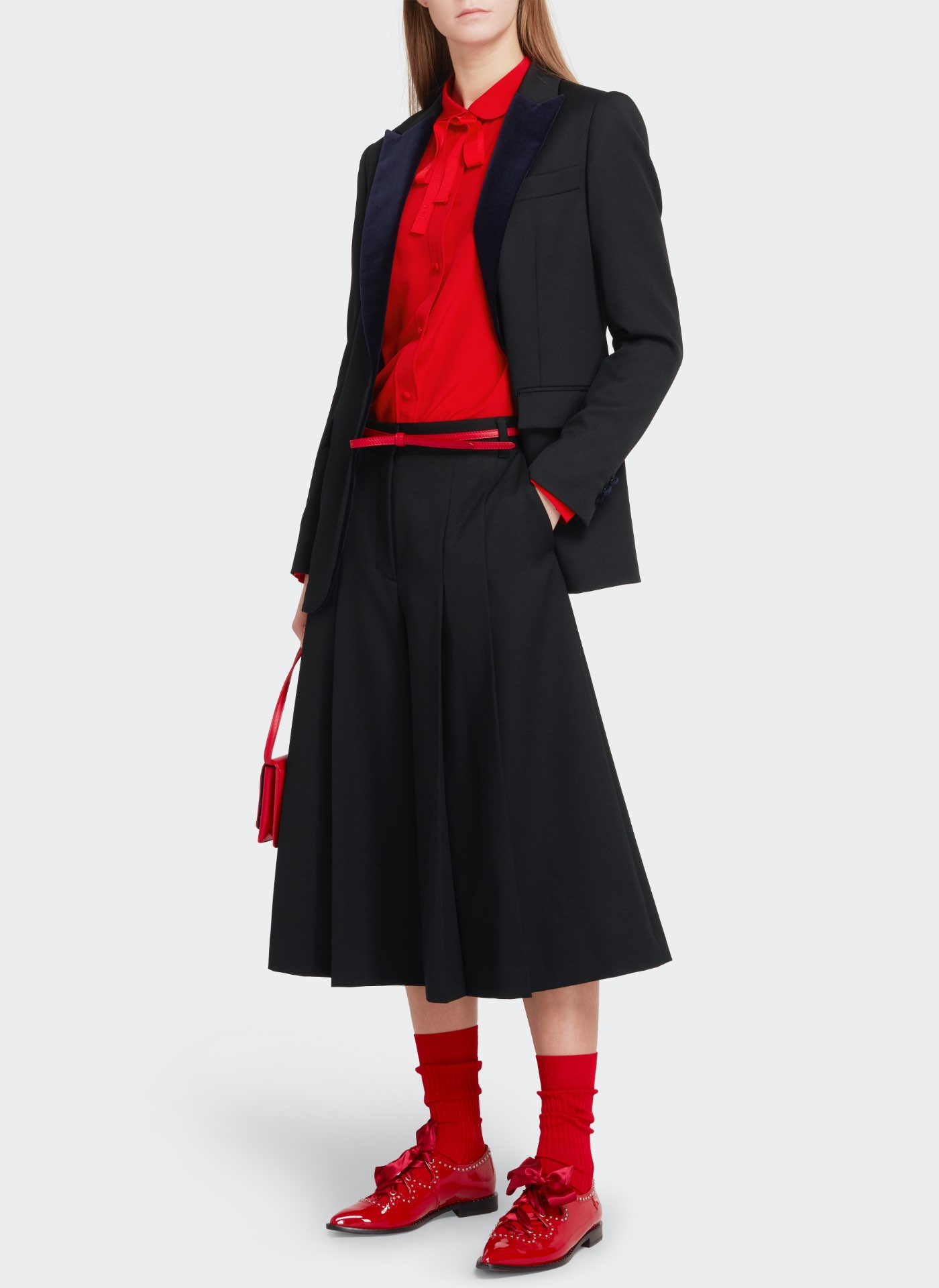 Womenswear model wearing black J&M skirt with a black jacket holding a red leather bag, red shoes and red belt, red socks
