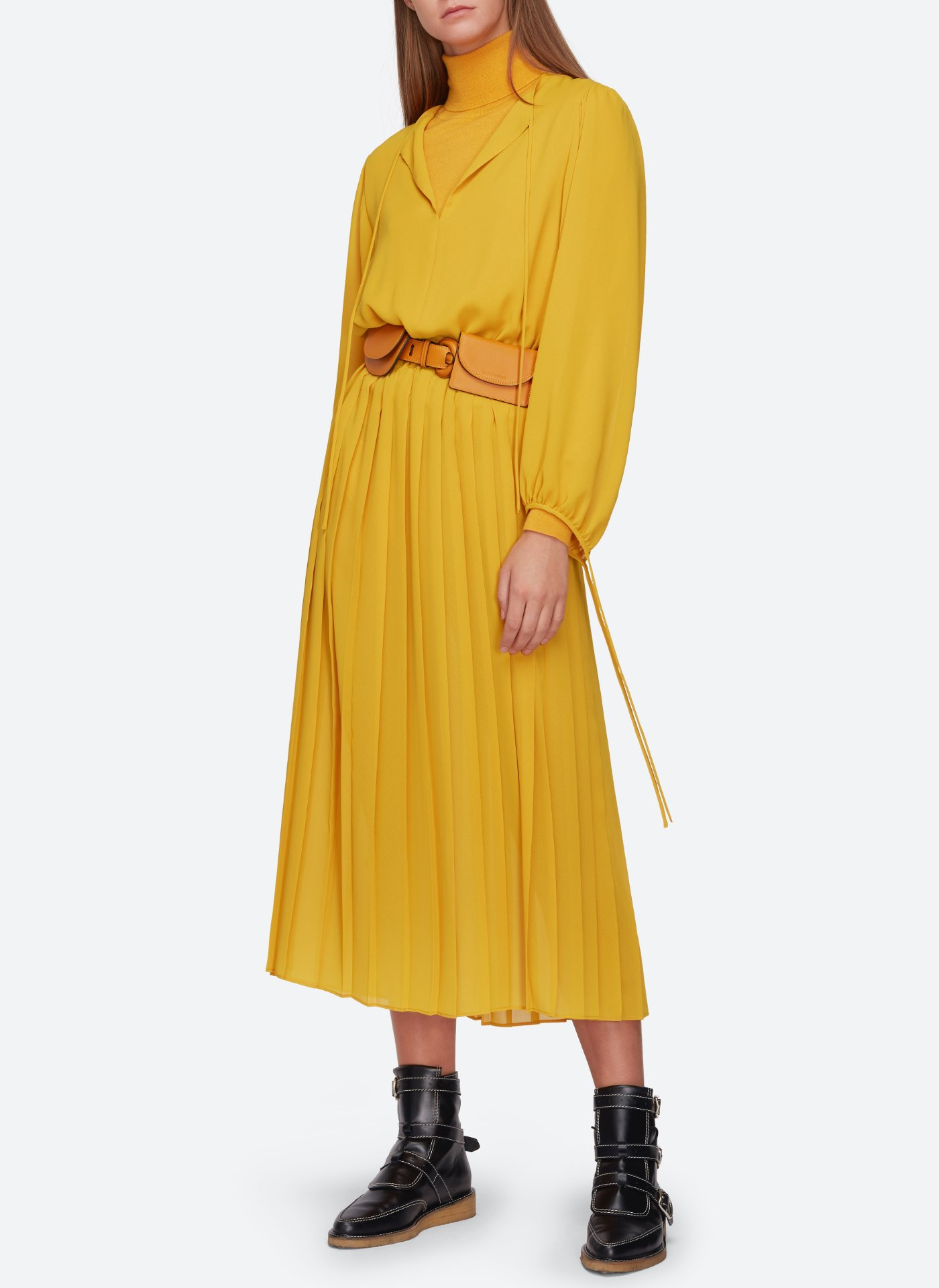 Womenswear model wearing a bright yellow dress with a light brown leather J&M belt and black leather shoes