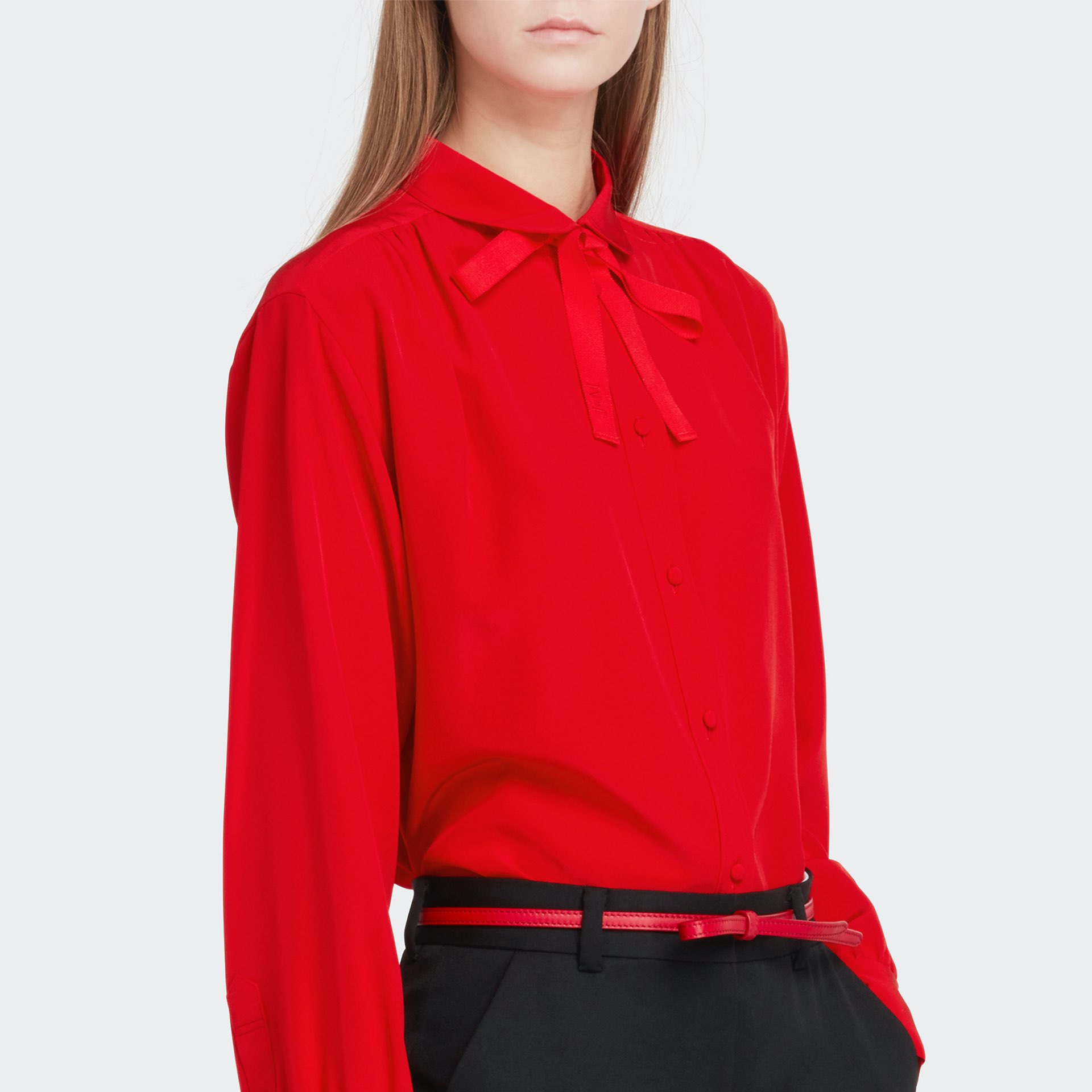womenswear model wearing bright red shirt, red belt and black trousers