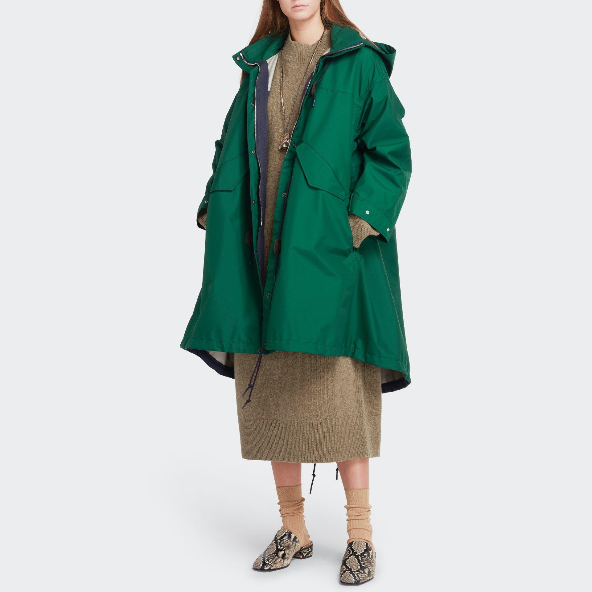 Womenswear model wearing pale moss long sweater dress with a deep green raincoat over her