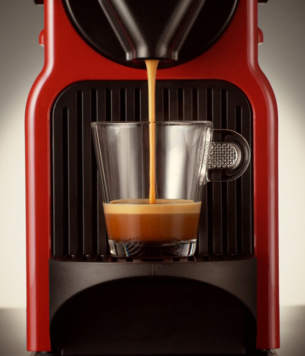 Coffee maker in red colour making a coffee cup