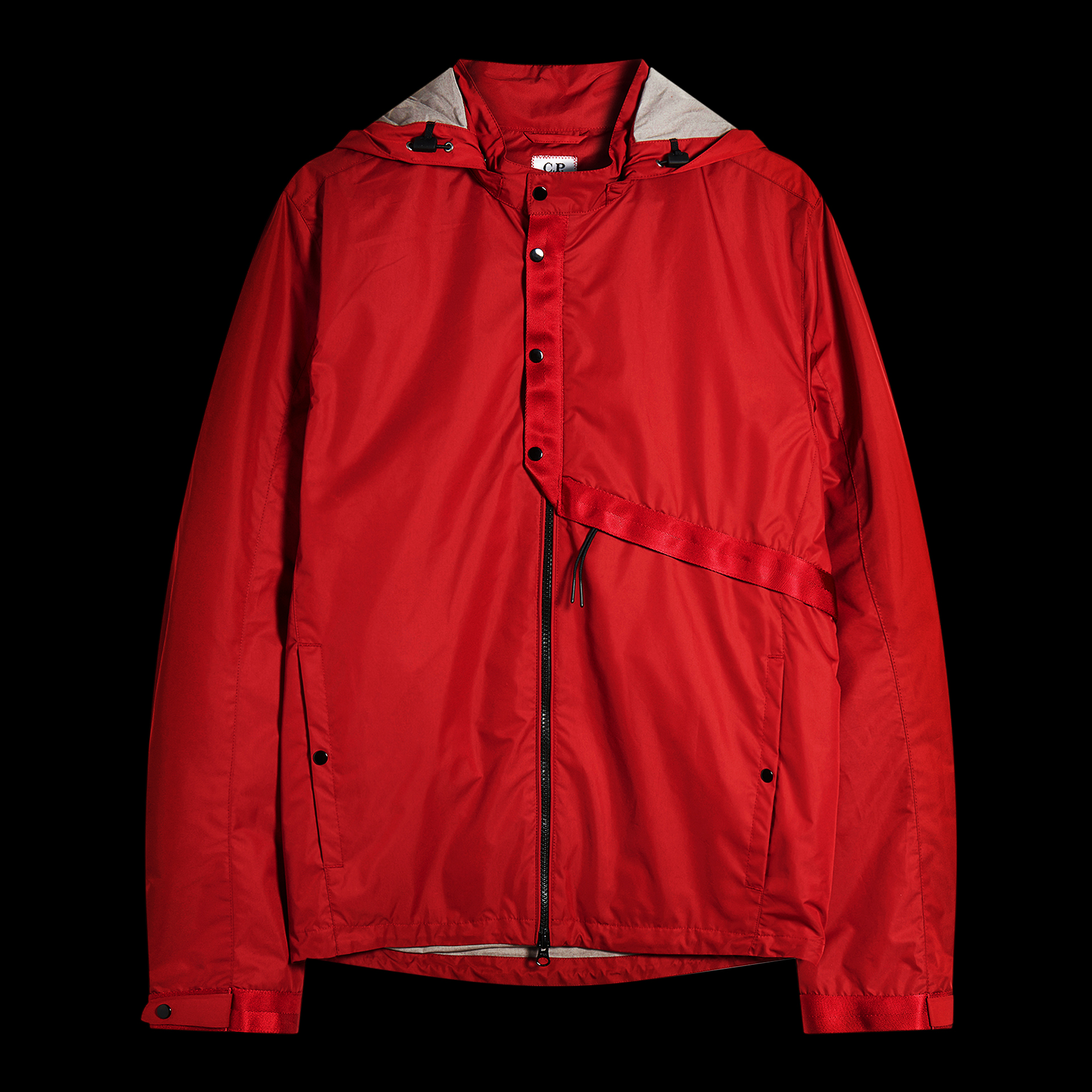 Red C.P. Company rain coat on black background