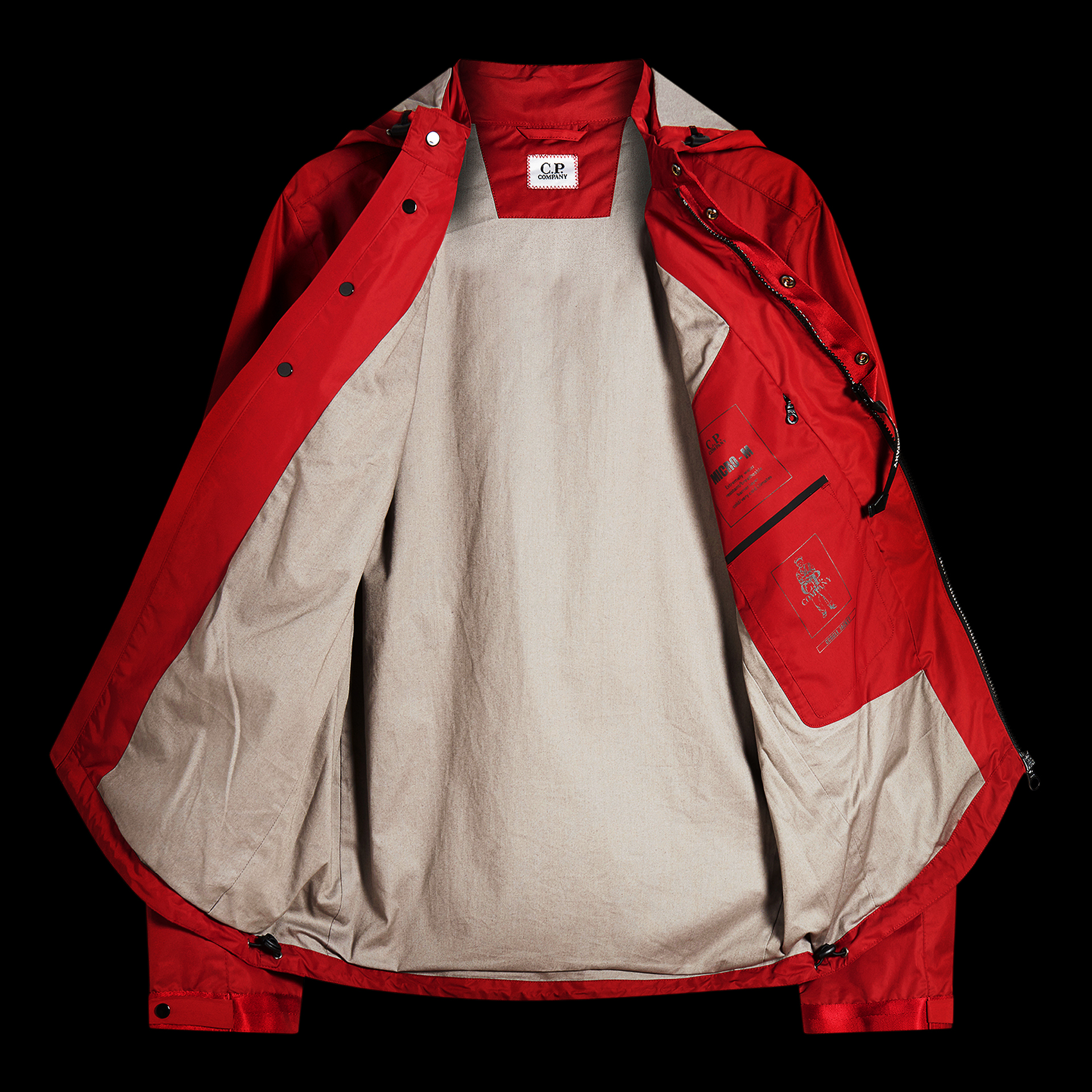 Red C.P. Company rain coat on black background open front shot