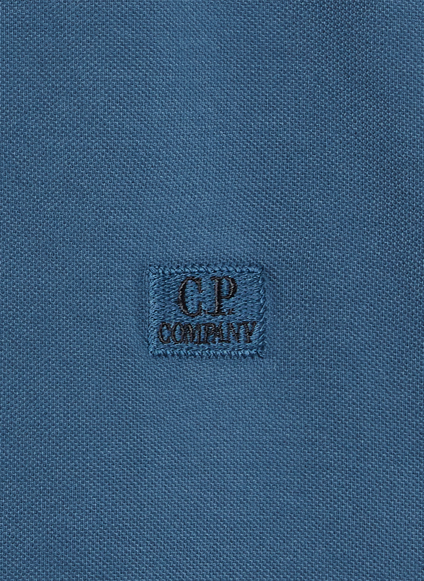 C.P. company logo embroidered on light navy blue textile