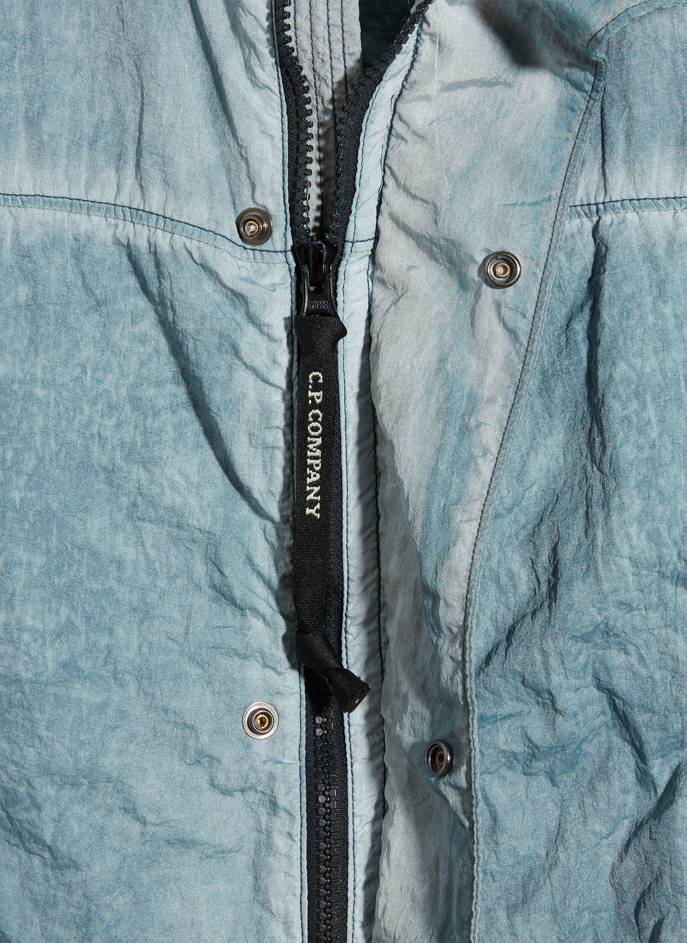 Detail shot of a black zipper of a washed out blue C.P. Company jacket