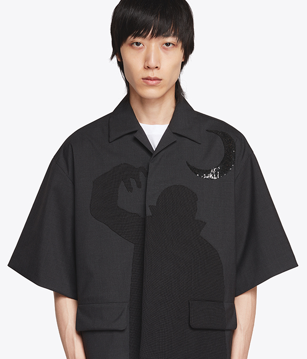 Asian menswear model wearing a black cropped sleeve over shirt