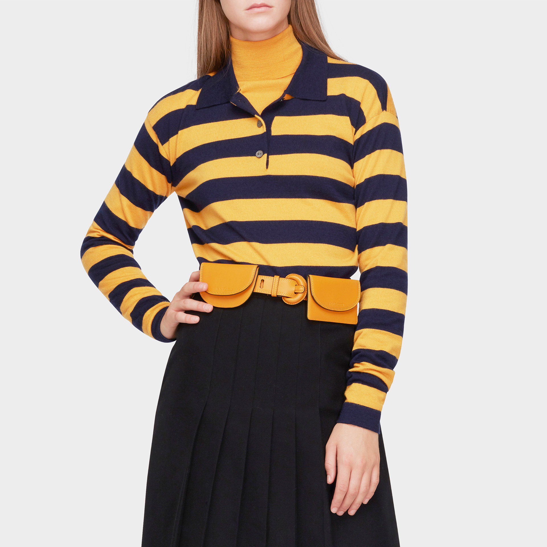 womenswear model wearing a yellow and black striped top with black skirt and light brown leather J&M belt with small compartments