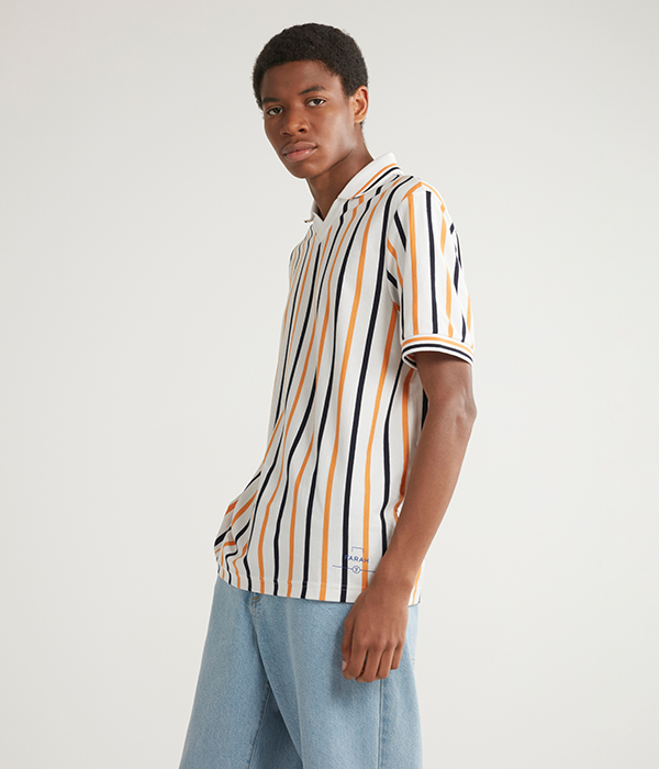 Menswear model wearing blue jeans and yellow striped t-shirt