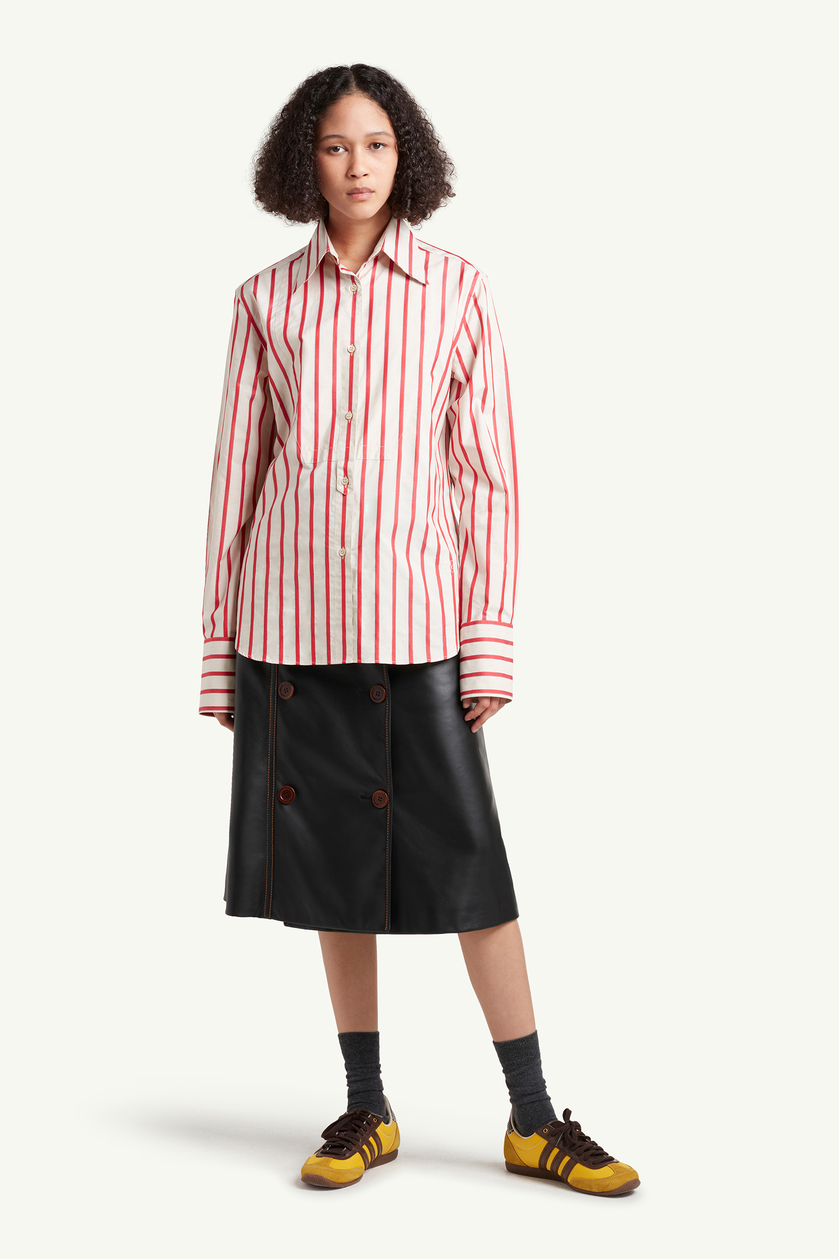 Wales Bonner Menswear Model wearing a red striped shirt and leather skirt | LRP