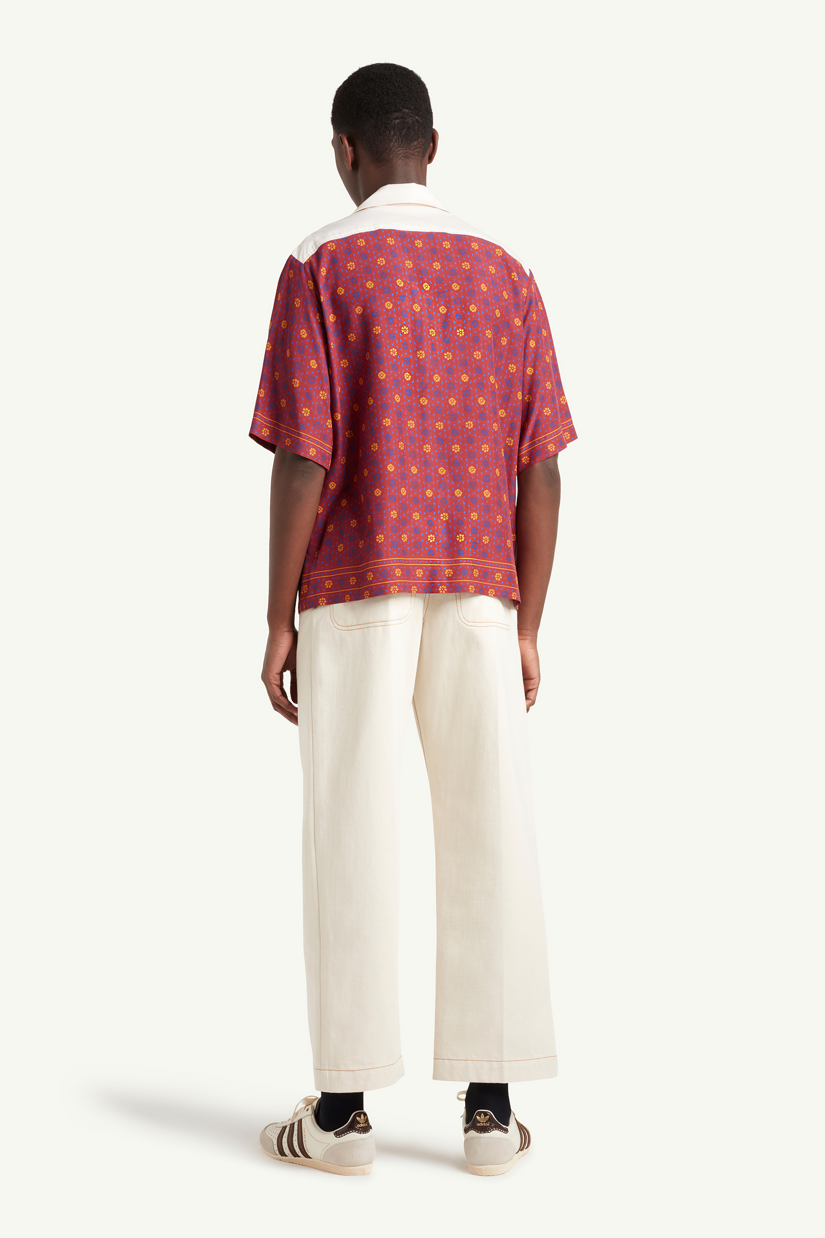 Wales Bonner Menswear Model wearing a white and burgundy pattern shirt with white cropped trousers | LRP