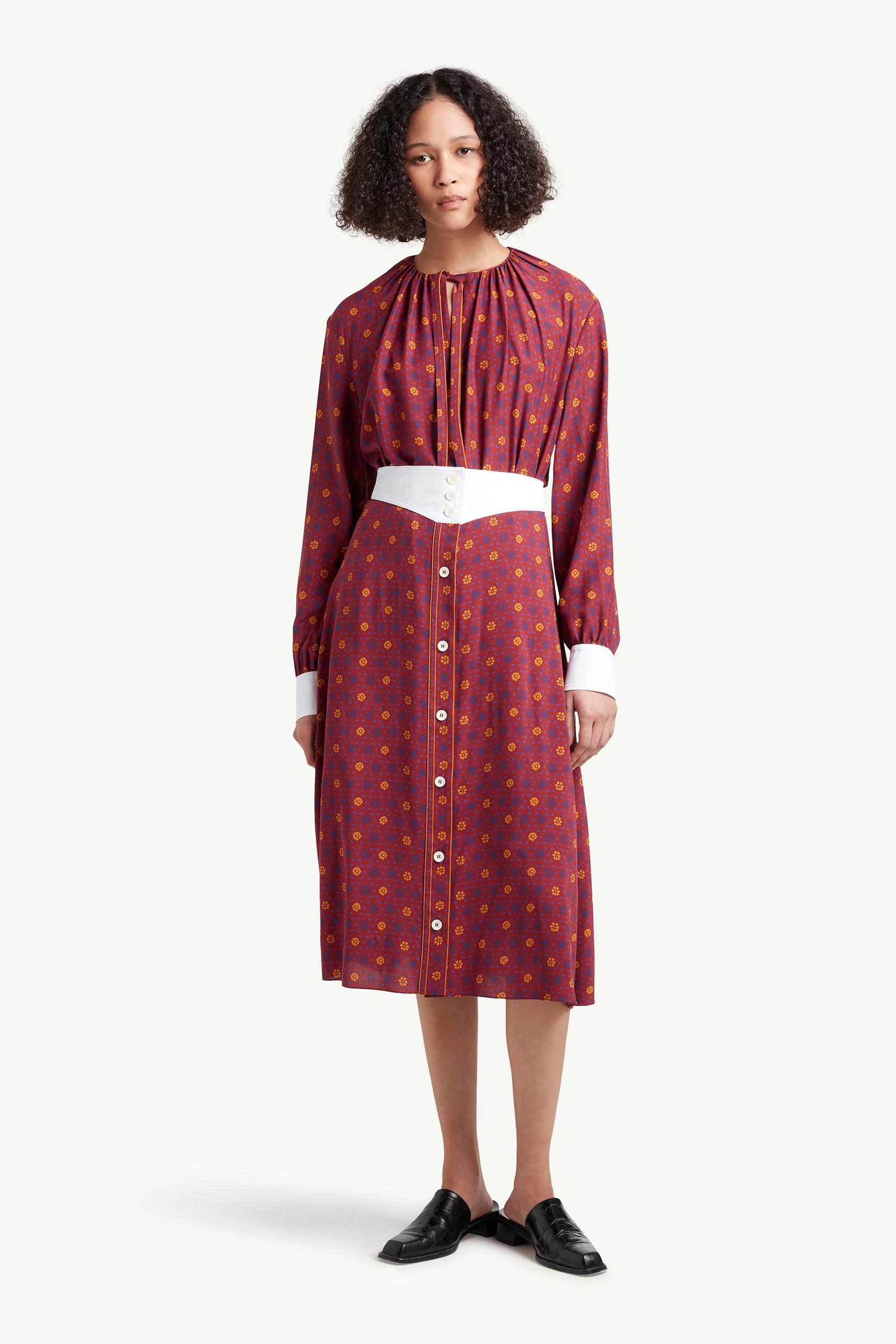 Womenswear model wearing  Wales Bonner dress in burgundy with pattern and white belt | LRP