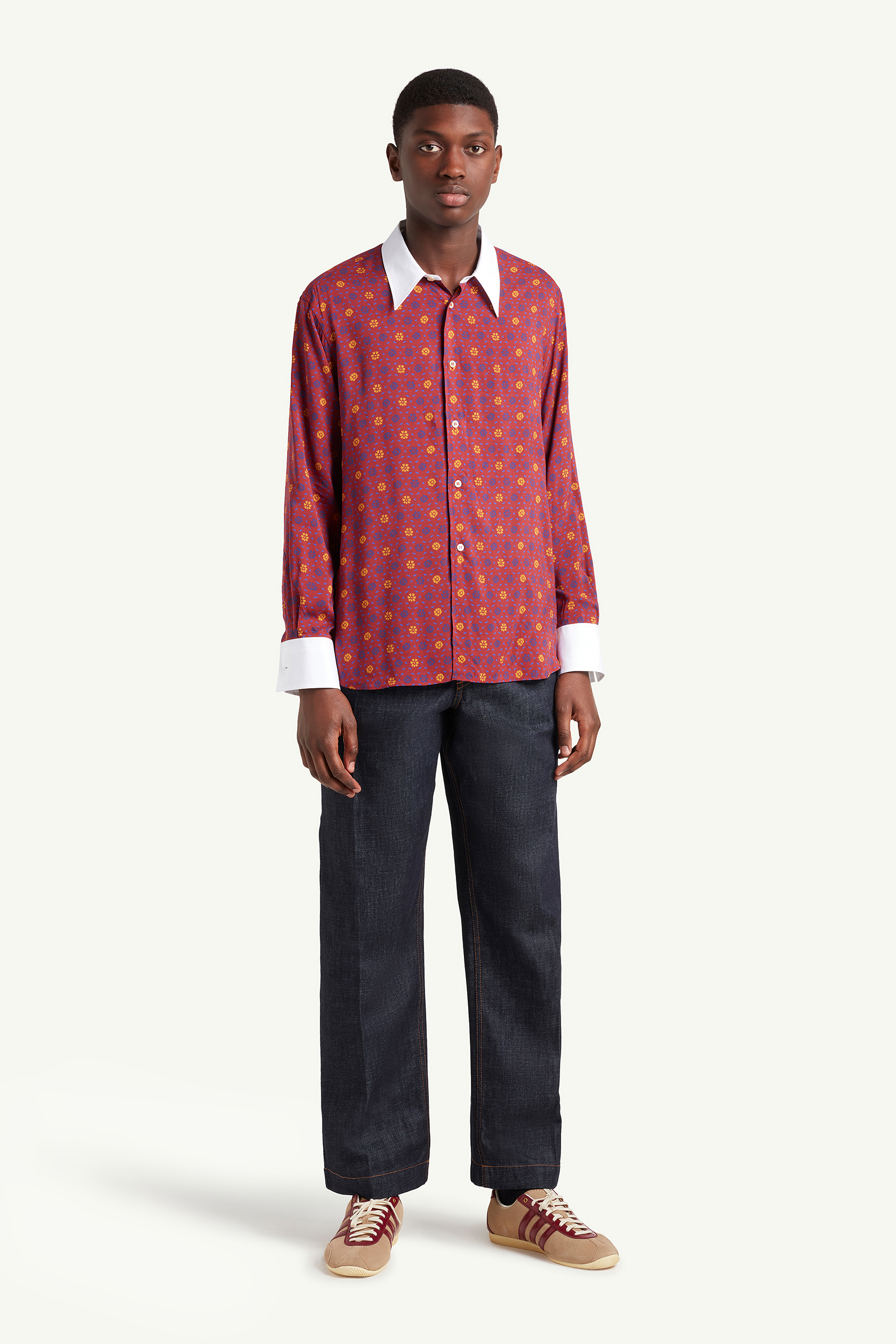 Wales Bonner Menswear Model wearing a white and burgundy pattern shirt with black cropped trousers | LRP
