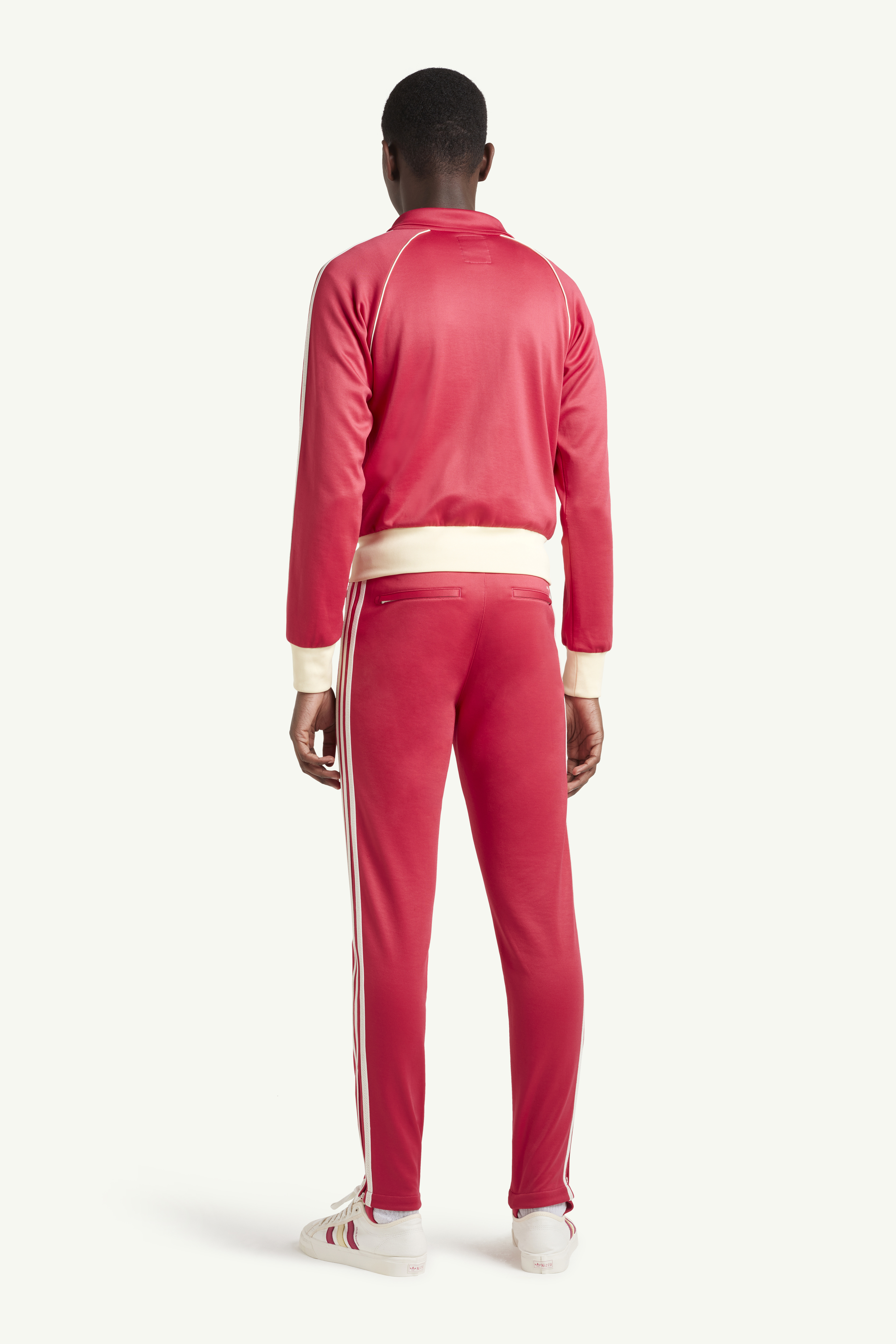 Back shot of Menswear model wearing Wales Bonner Bright red sweat suit with white trainers | LRP