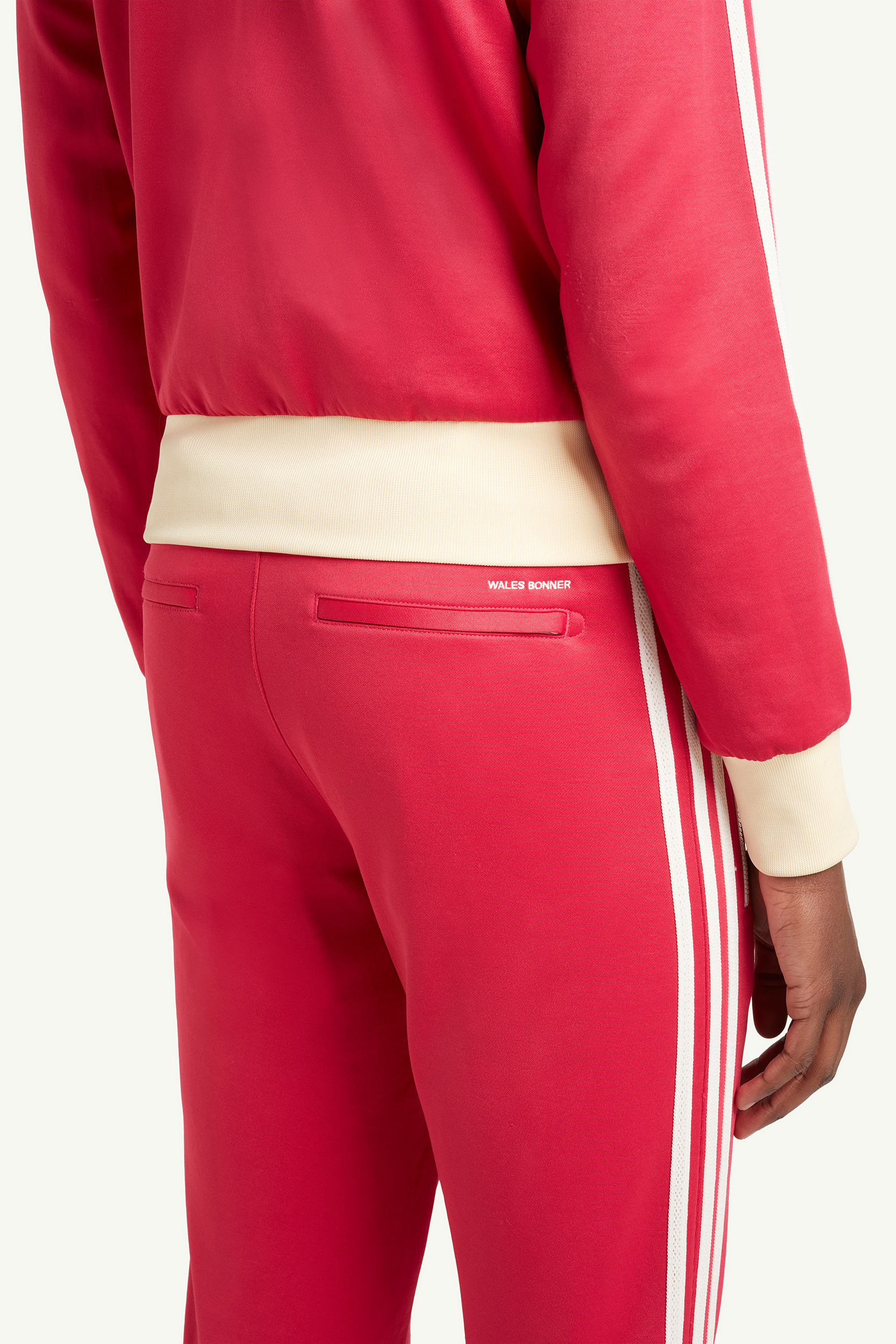 Closeup shot of detailing in the back of Menswear model wearing Wales Bonner Bright red sweat suit with white trainers | LRP