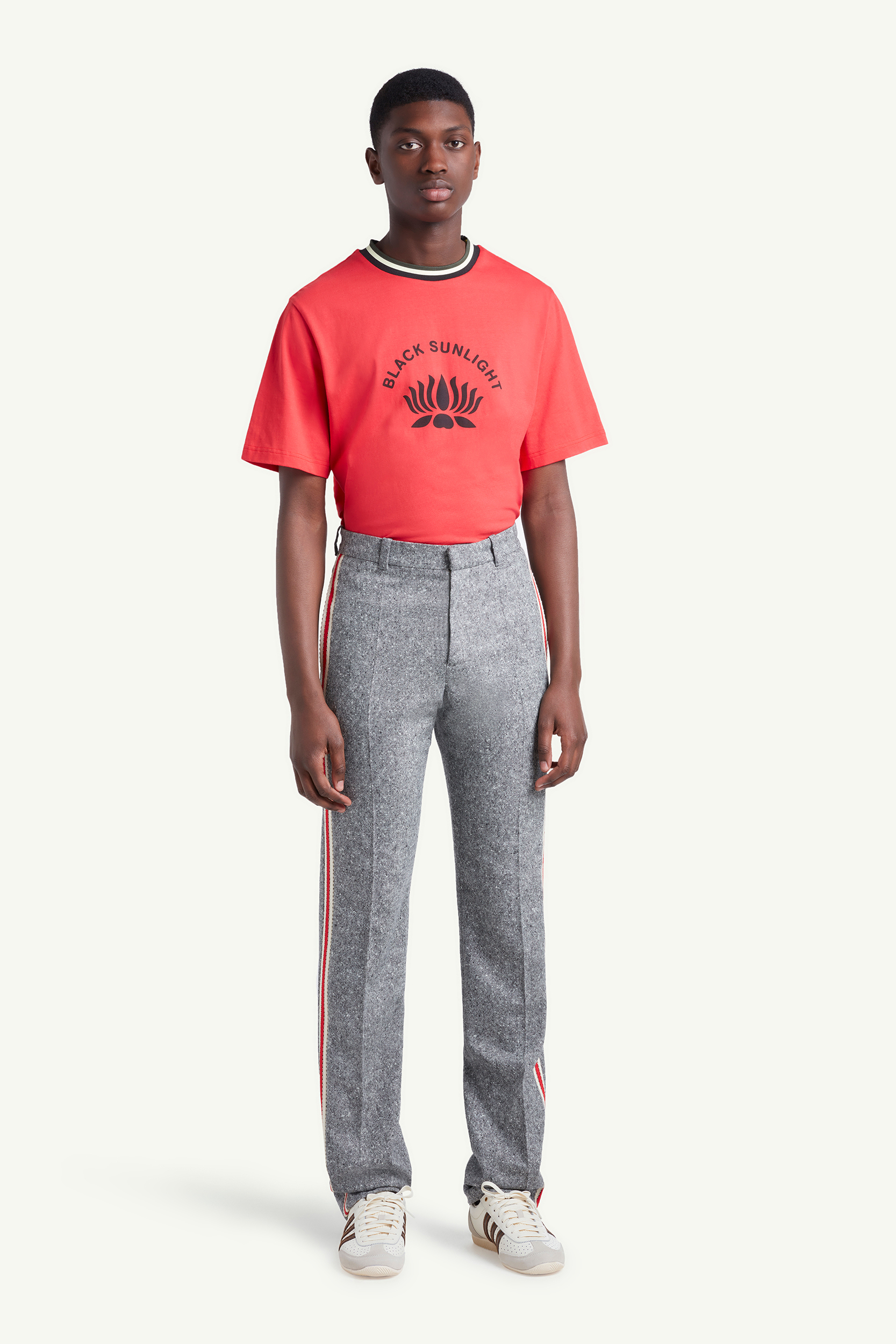 Menswear model wearing Wales Bonner red shirt with grey joggers and white trainers | LRP