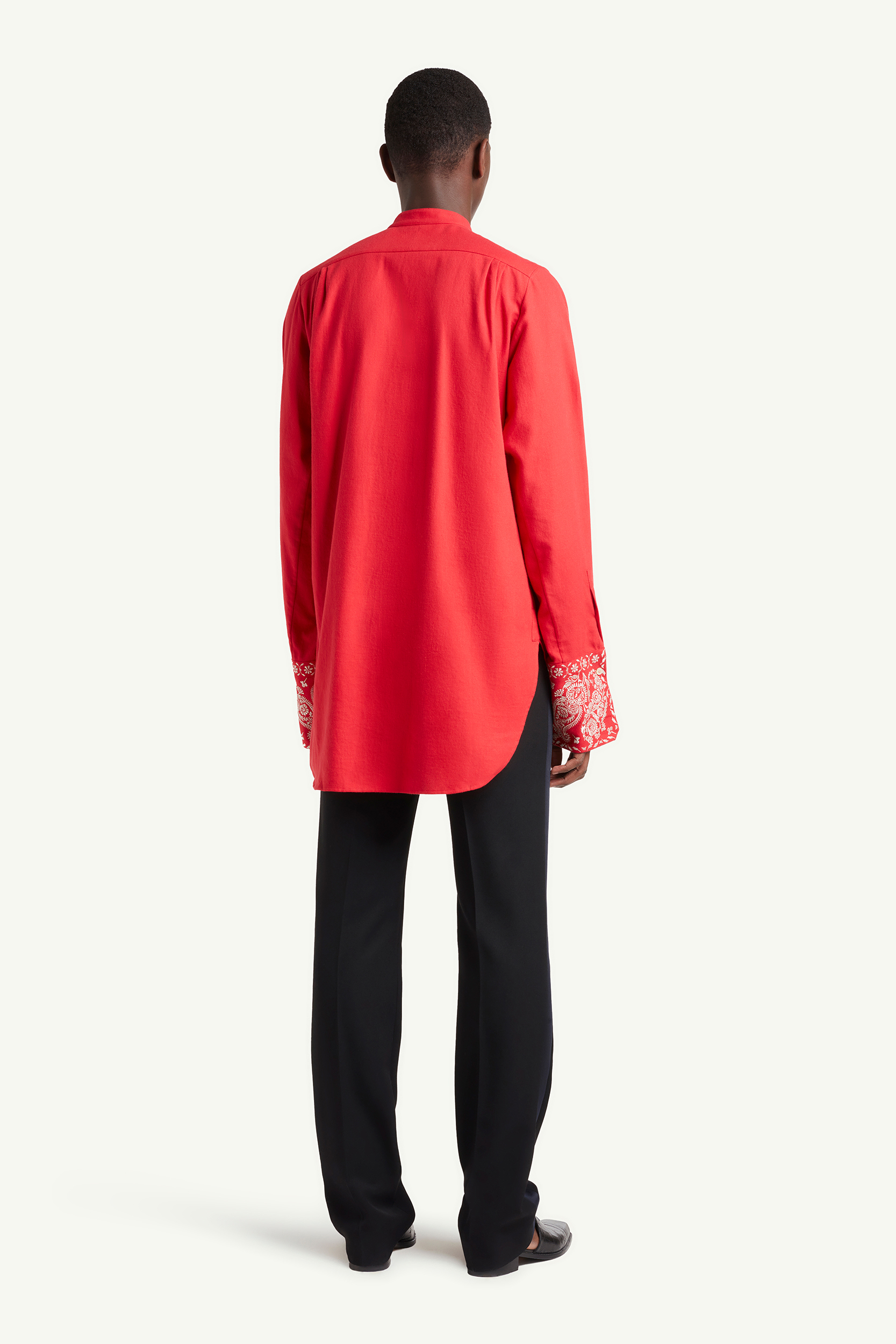 Back shot of Menswear model wearing Wales Bonner red long shit and black smart trousers | LRP