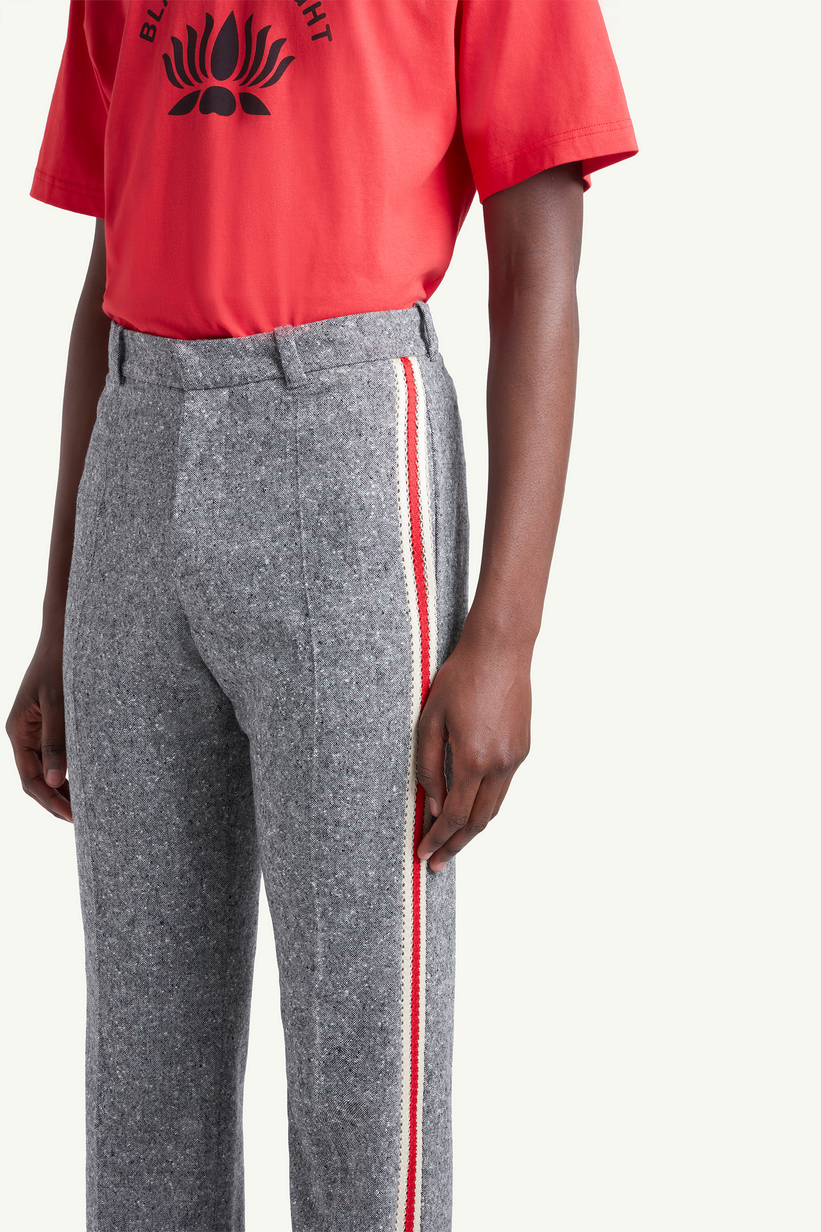 Detail shot of Menswear model wearing Wales Bonner red shirt with grey joggers and white trainers | LRP