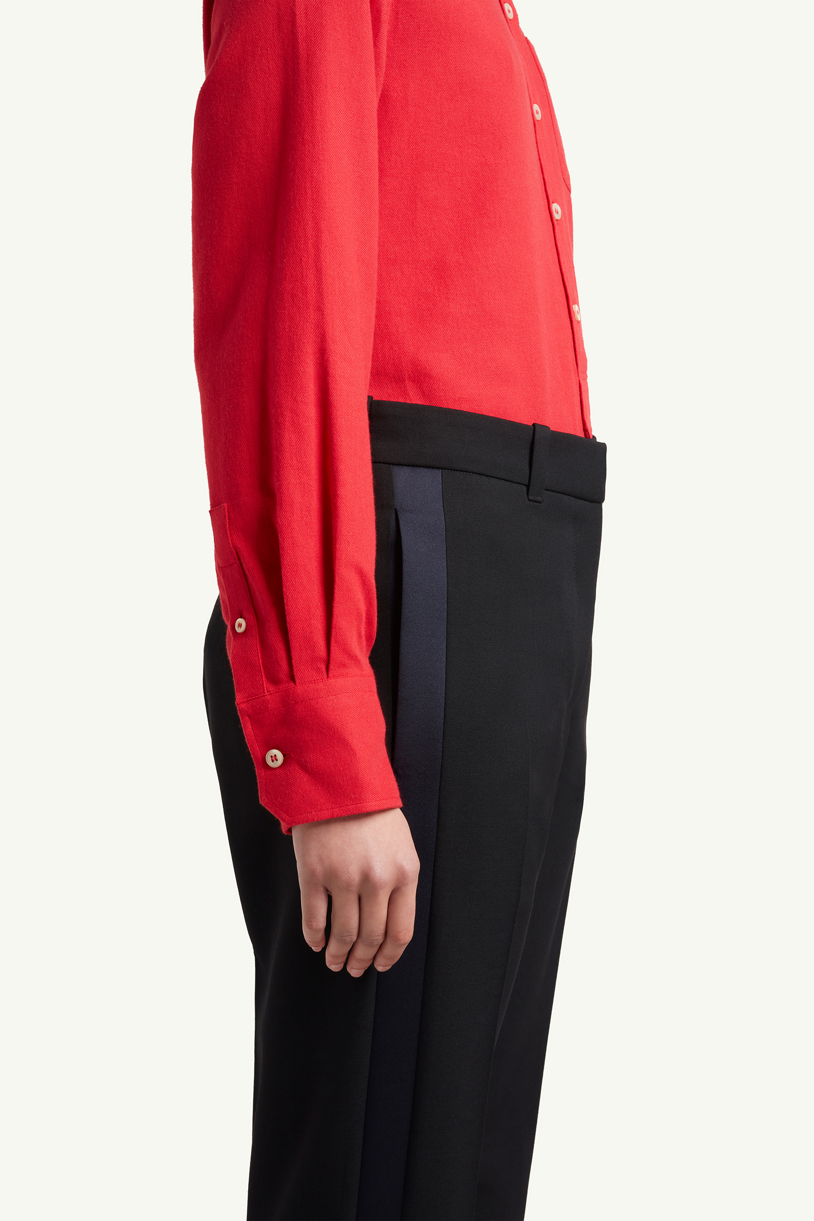 Side detail shot of Wales Bonner red shirt and black smart trousers