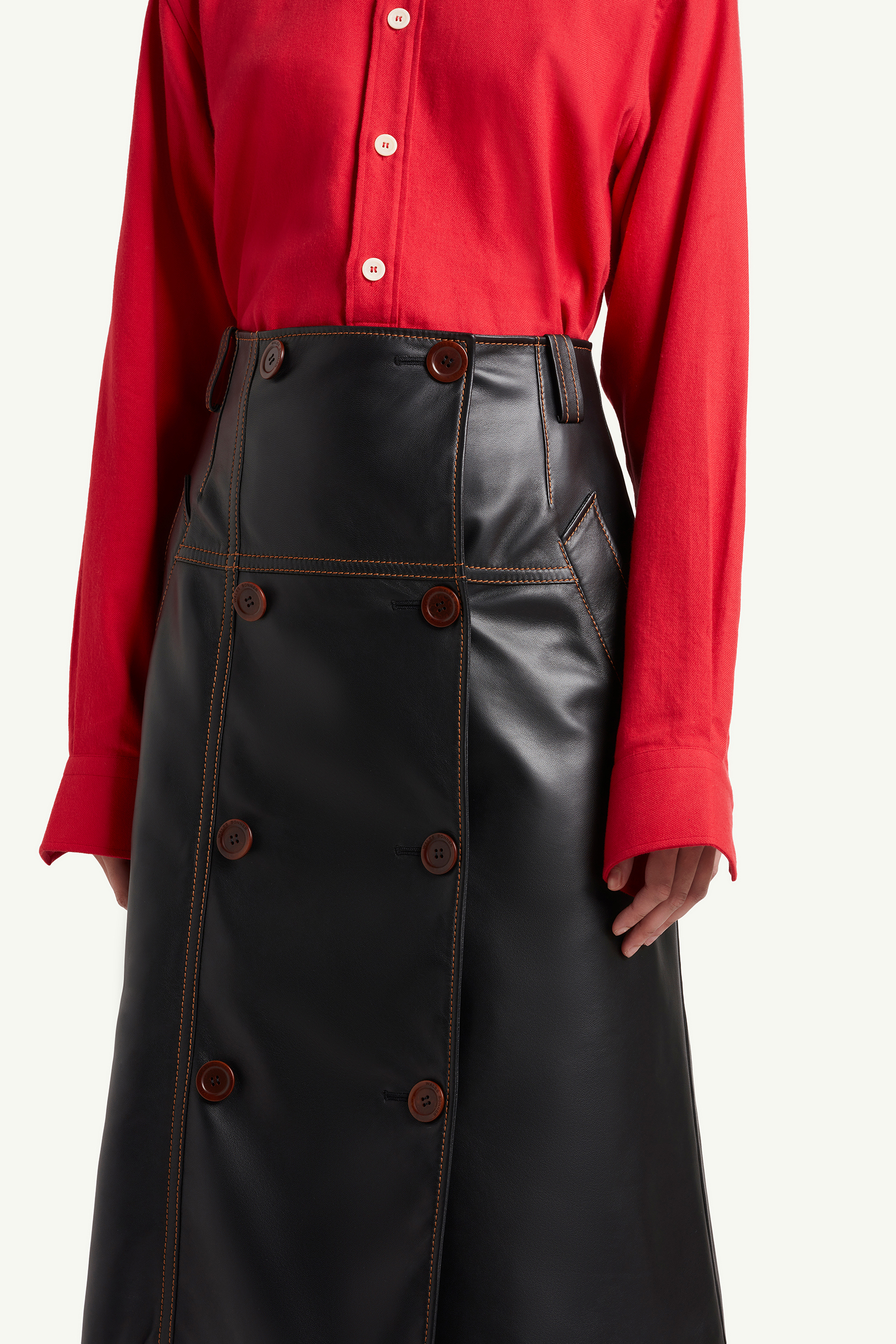 Detail shot of the Wales Bonner leather skirt with Red Shirt on womenswear model