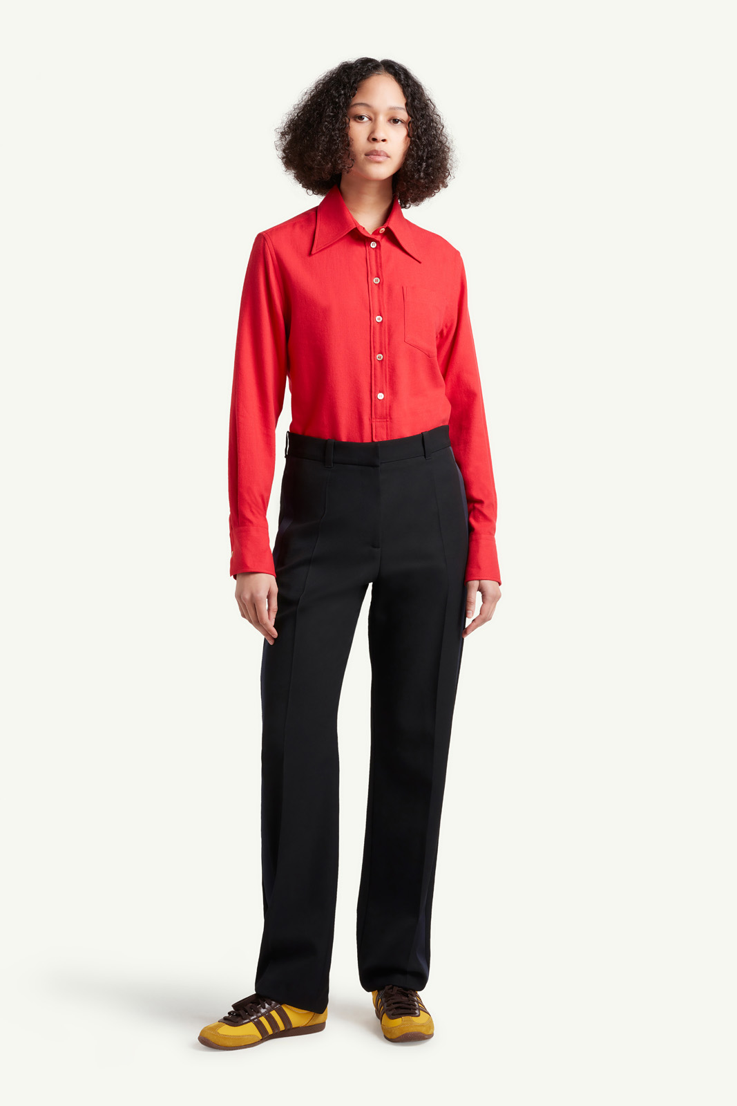 Womenswear model wearing Wales Bonner red shirt and smart black trousers with multi colour trainers