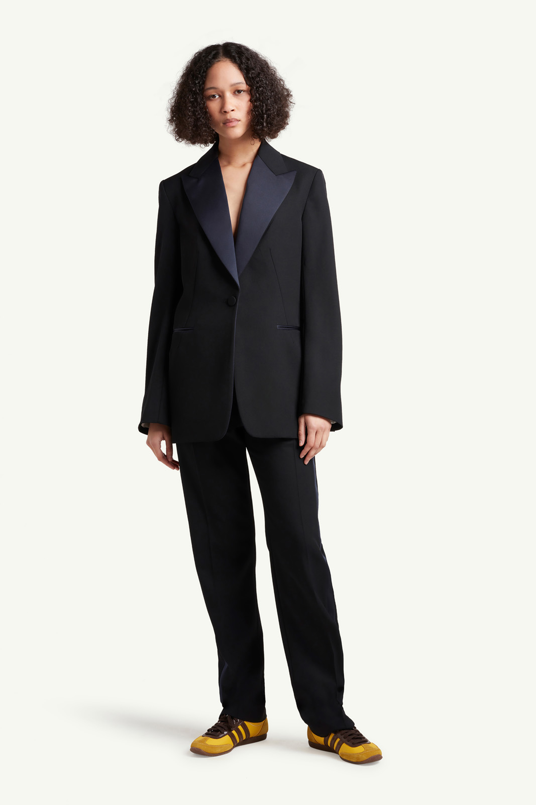 Womenswear model wearing black Wales Bonner suit with multi colour trainers