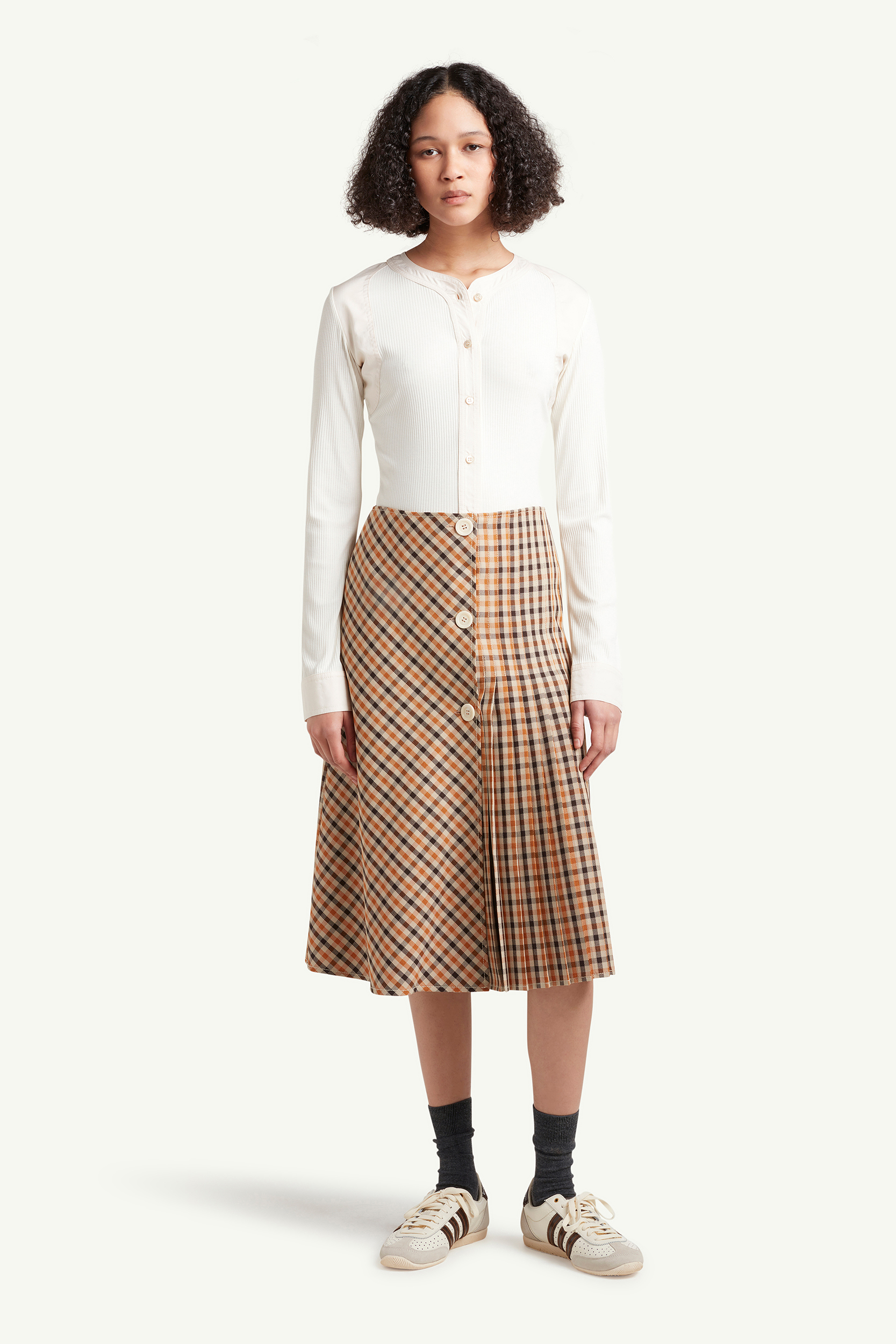 Womenswear Model wearing light brown checkered skirt with white top