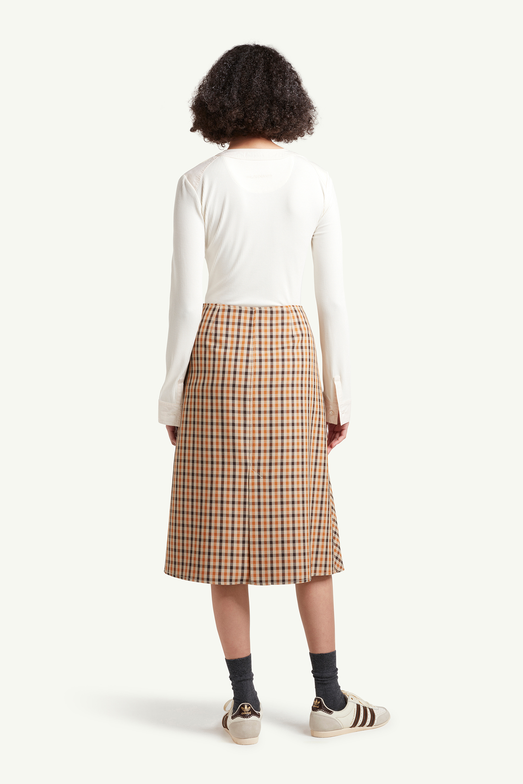 back shot of Womenswear Model wearing light brown checkered skirt with white top