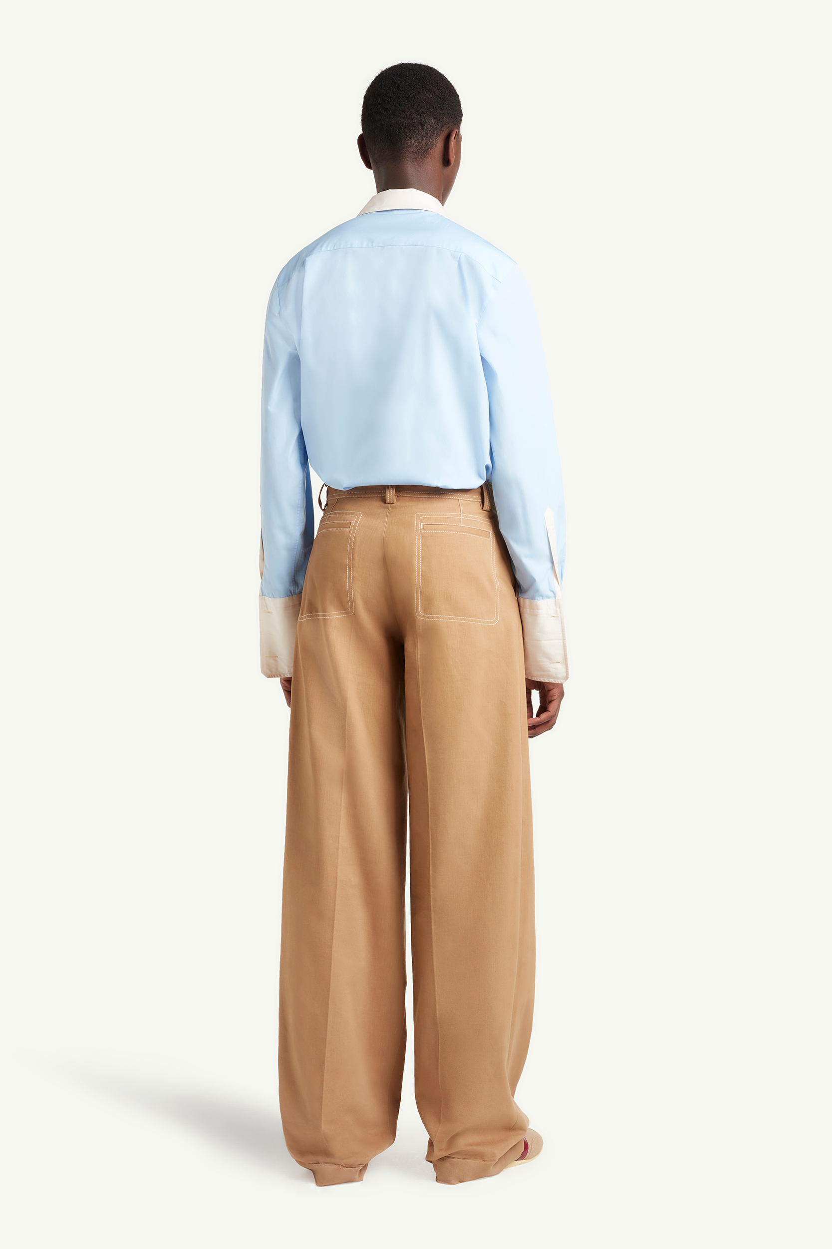 back shot of Menswear Model wearing light brown smart trousers with light blue top and white trainers  | eCommerce Photography London | LRP