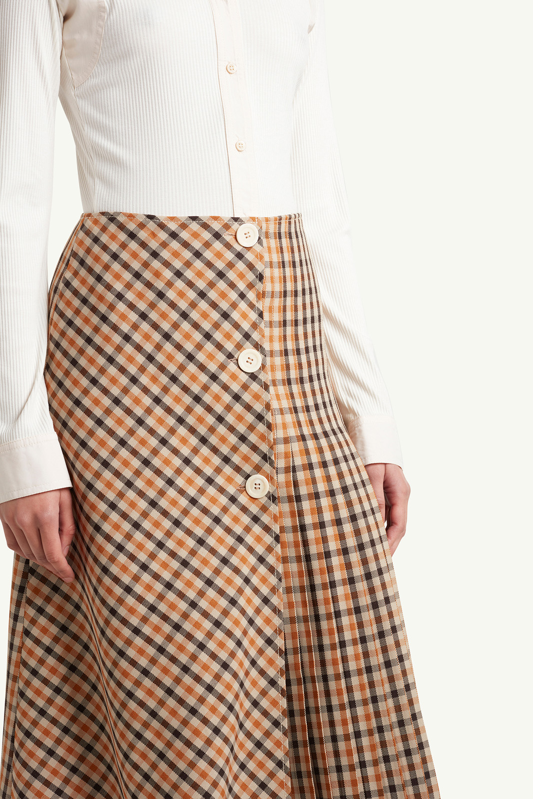 close up shot of Womenswear Model wearing light brown checkered skirt with white top