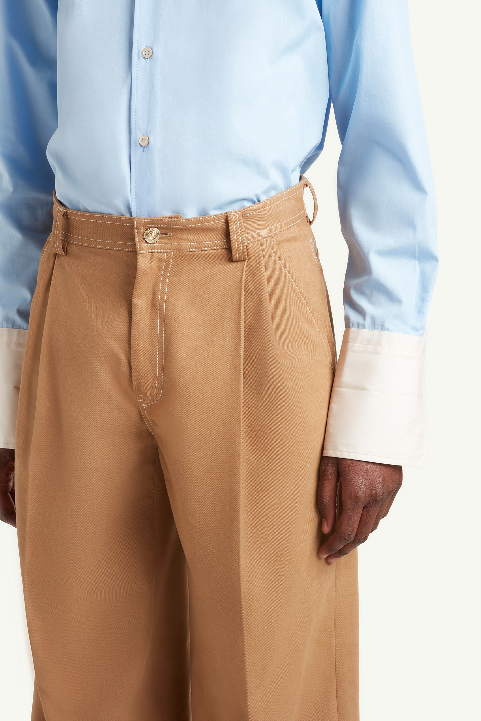 close up of Menswear Model wearing light brown smart trousers with light blue top and white trainers  | eCommerce Photography London | LRP