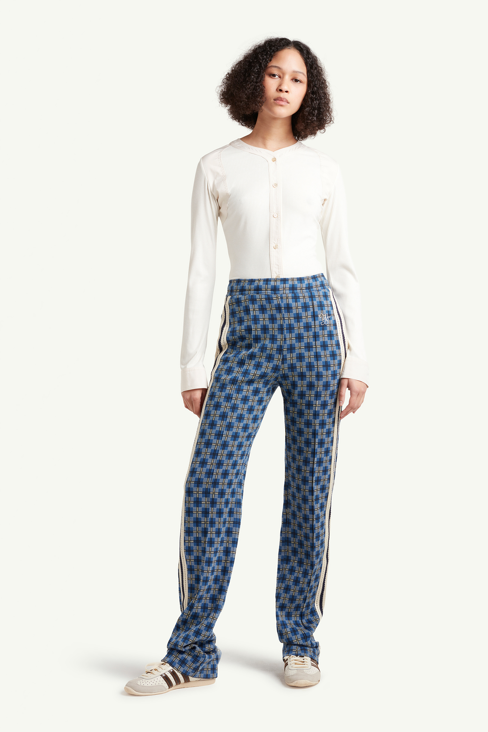 Womenswear model wearing Detail shot of Wales Bonner blue pattern trousers with white stripes on the side and white top