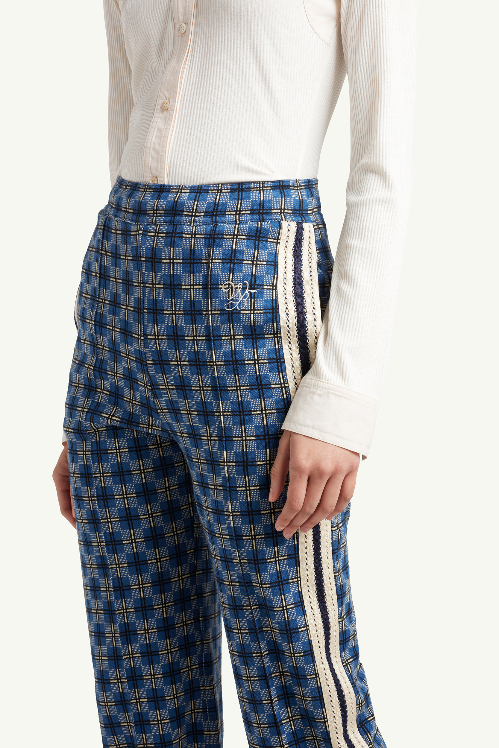 Detail shot of Wales Bonner blue pattern trousers with white stripes on the side