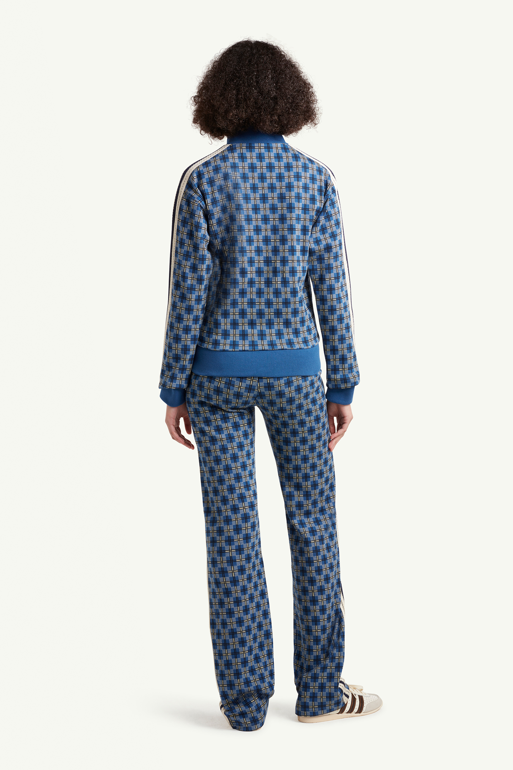 Backside shot of Womenswear model wearing Detail shot of Wales Bonner blue pattern trousers with white stripes on same pattern track top