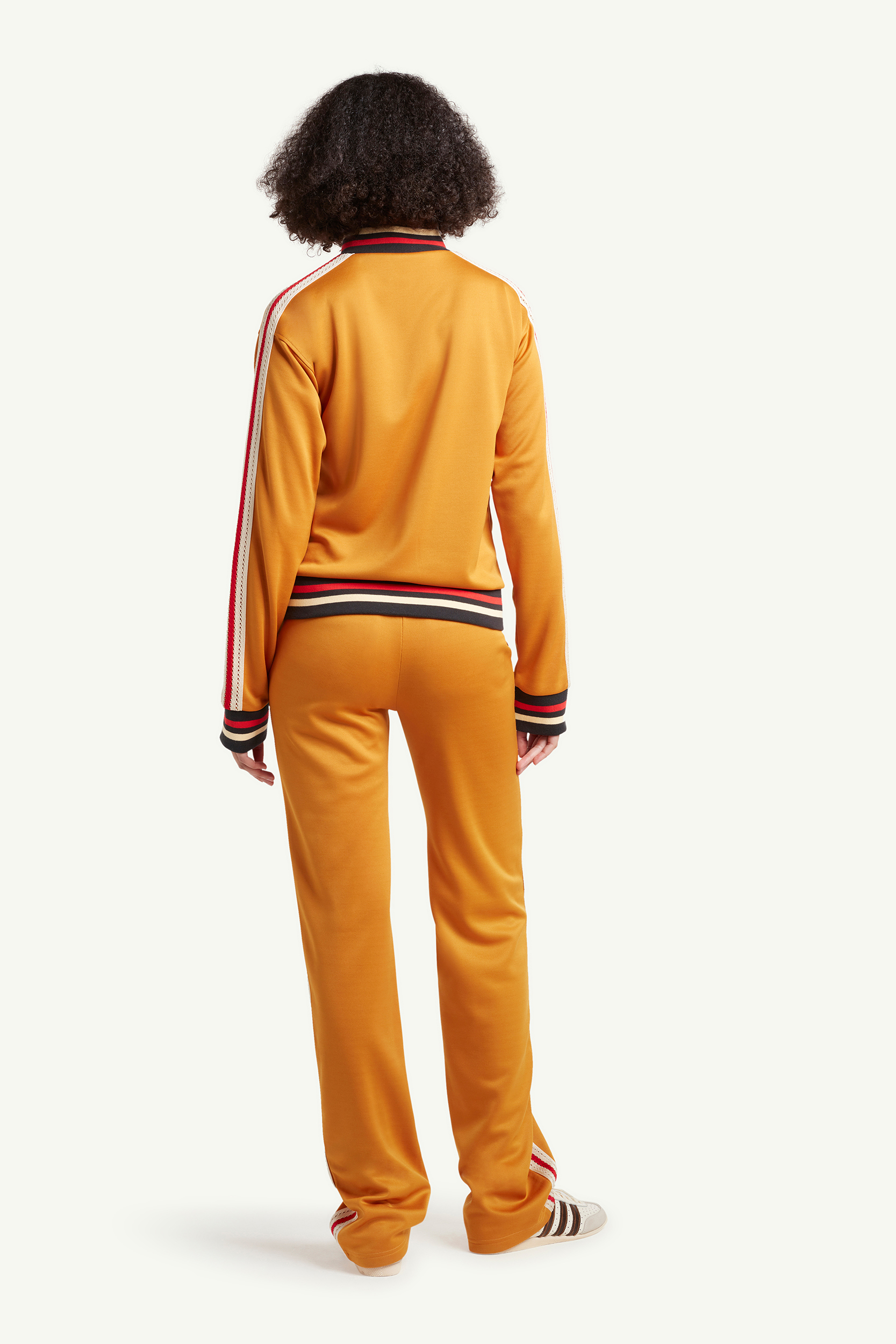 backside shot of womenswear model wearing mustard yellow Wales Bonner tracksuit with red and blue line detailing