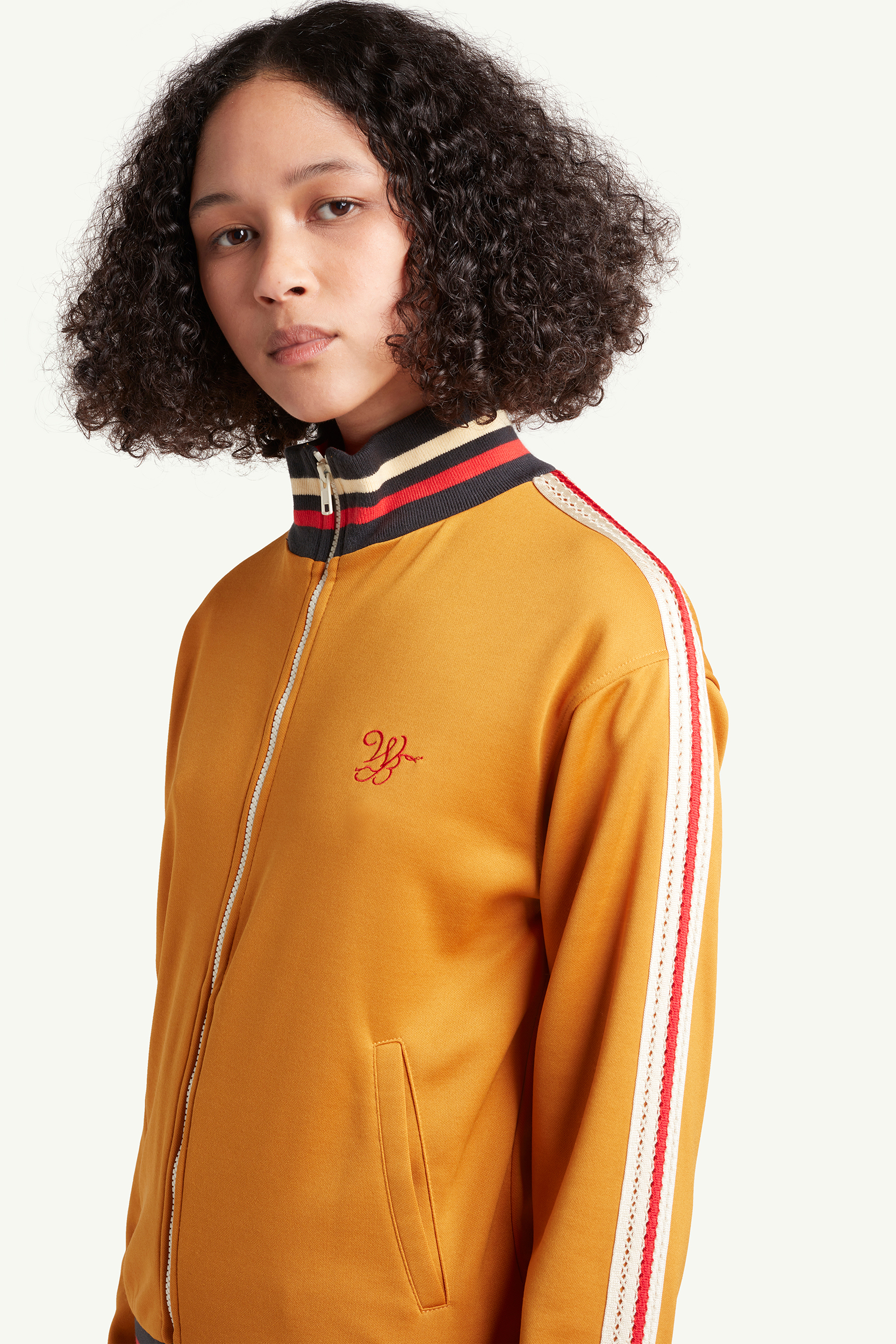 Portrait shot of a womenswear model wearing mustard yellow Wales Bonner tracksuit with red and blue line detailing